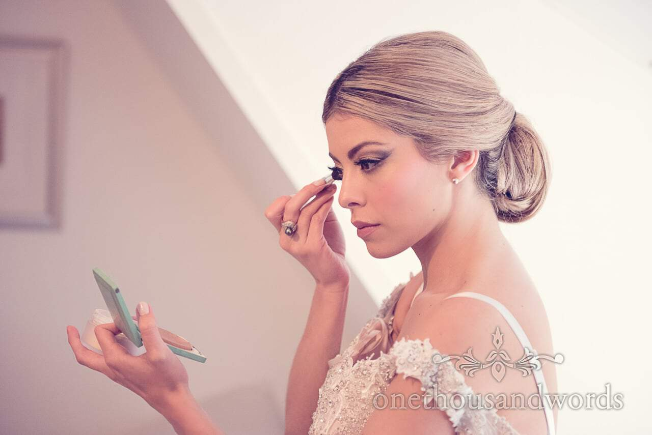 Beautiful bride in white dress adds wedding makeup
