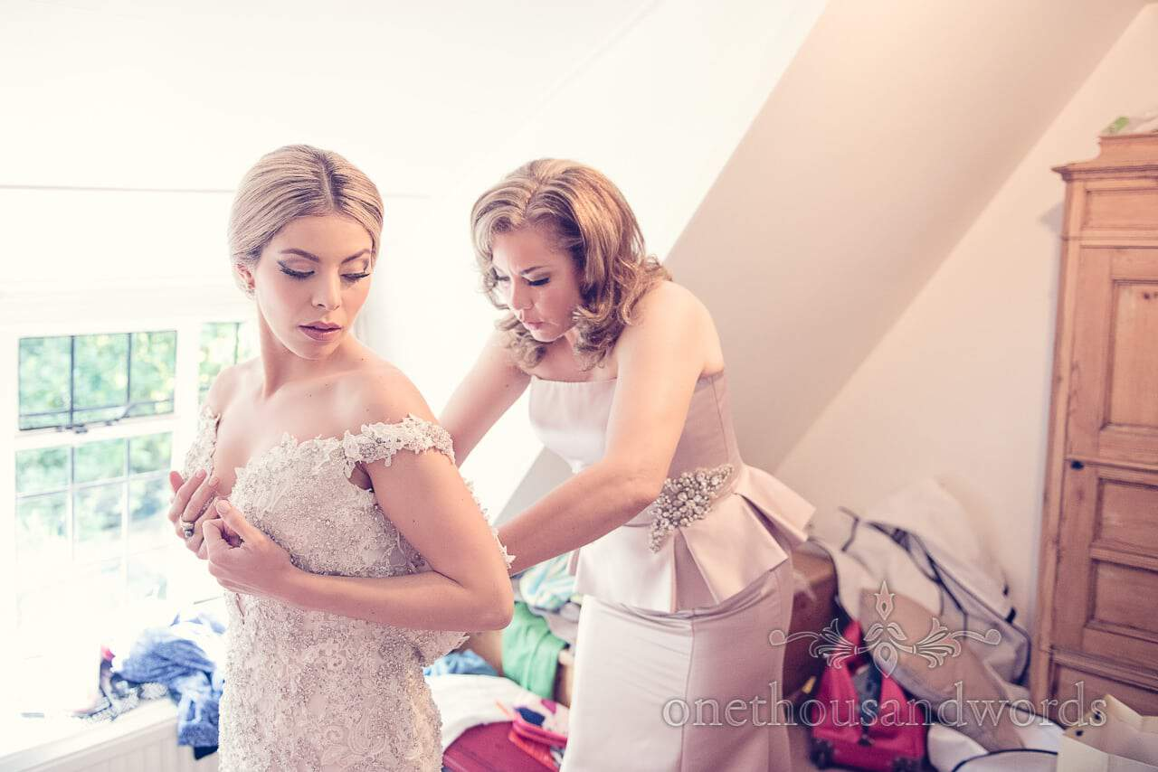 Beutiful bride is zipped into jewled wedding dress by her mother on wedding morning