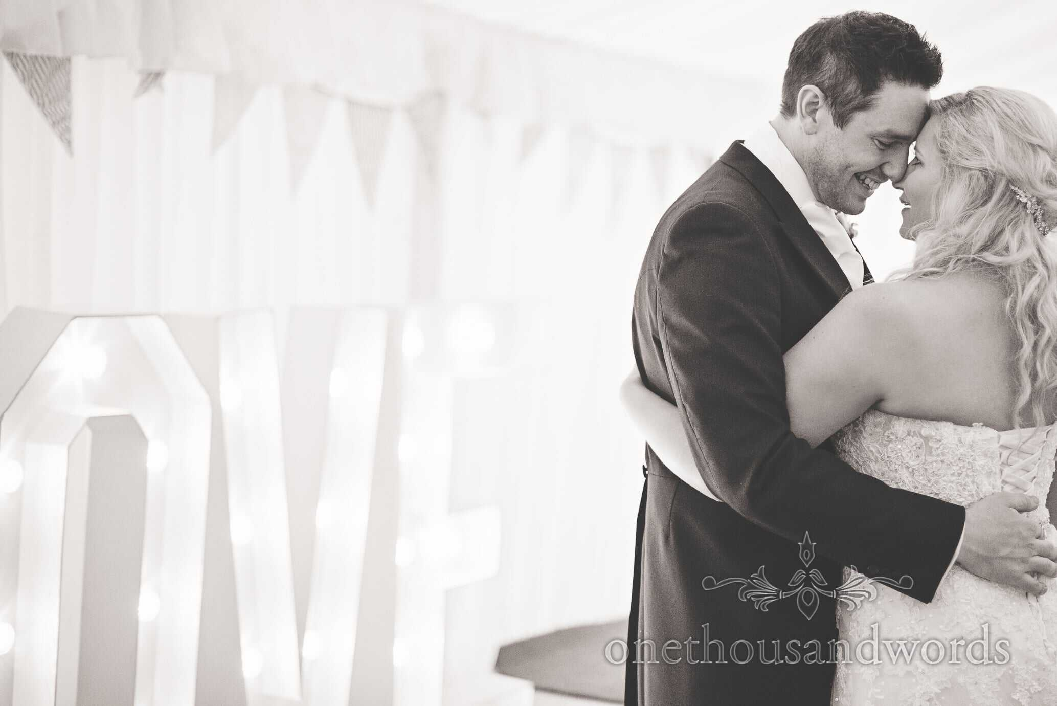 Black and white wedding photograph of bride and groom with love sign
