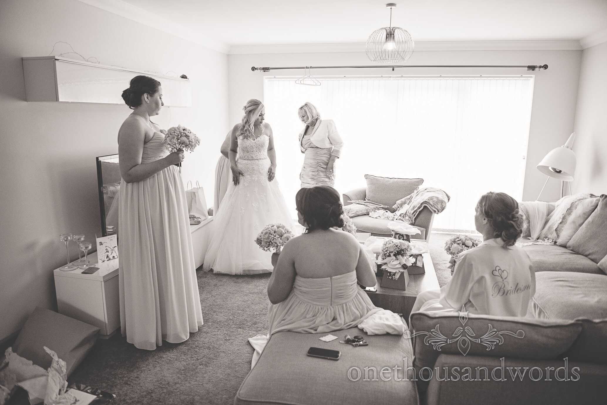 Black and white wedding photograph of bride being laced into wedding dress