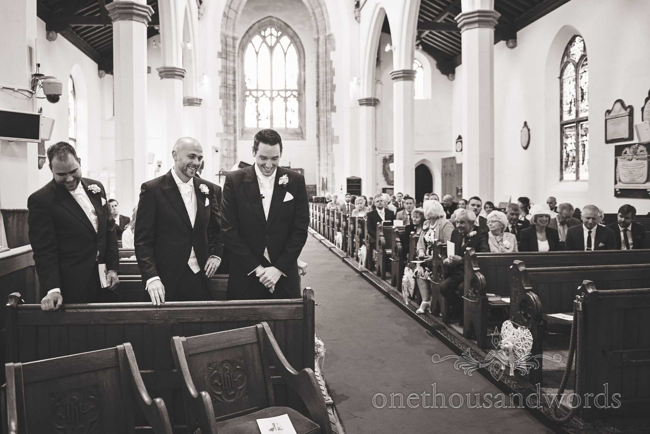 Black and White wedding photograph of groom and best men waiting in Church