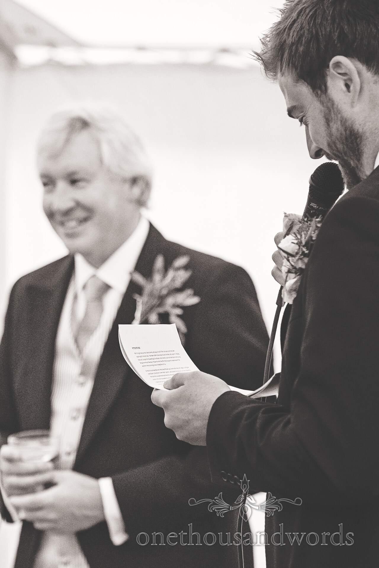 Black and White wedding photograph of groom reading speech