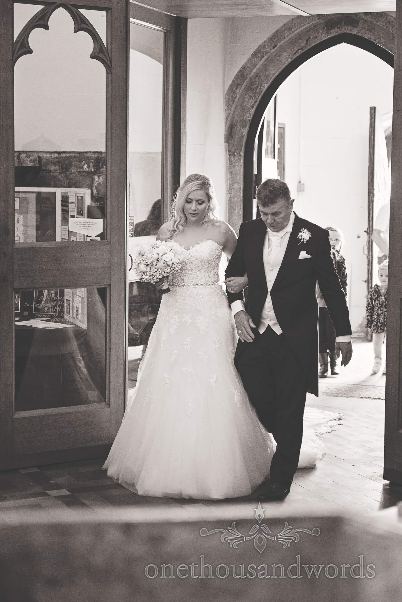 Black and white wedding photography of bride and father entering church wedding service