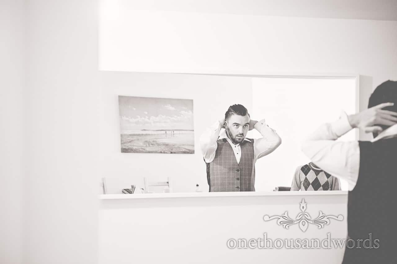 Black and white wedding photography of groom preparing for Rhinefield House Wedding