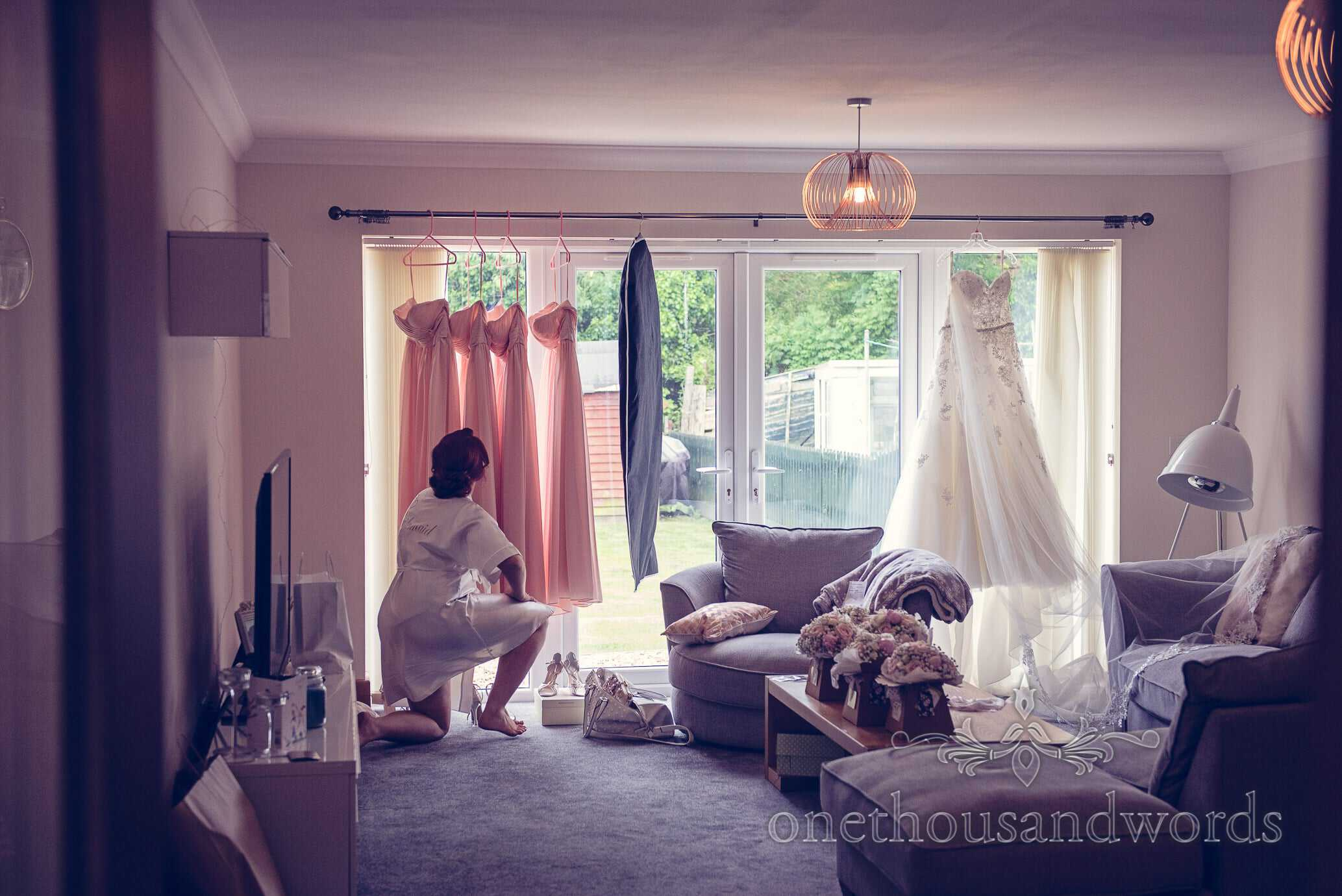 Bridal preparation room with dresses, flowers and shoes on wedding morning