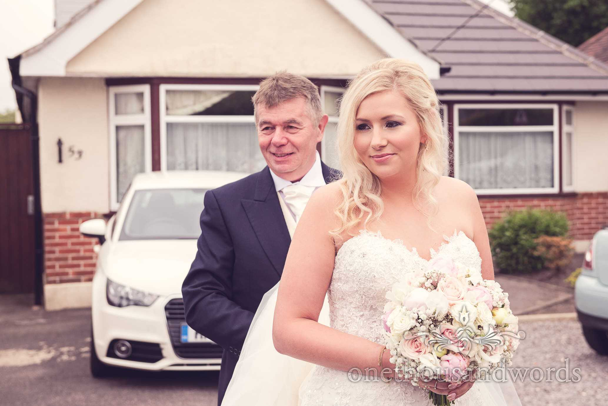 Bride and Father of the bride wait outside home for wedding cars