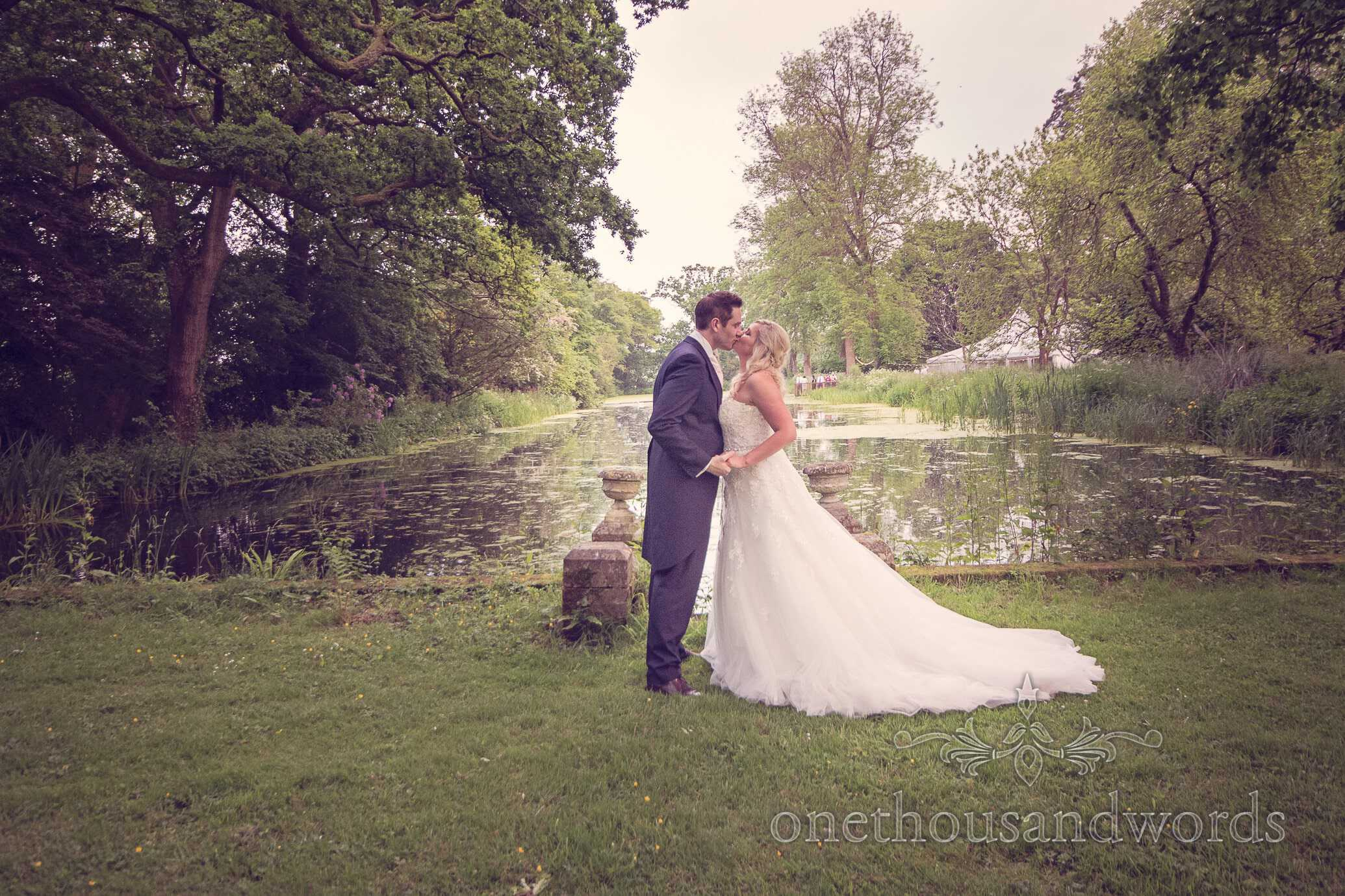 Bride and groom kiss next to lake at Deans Court Wedding