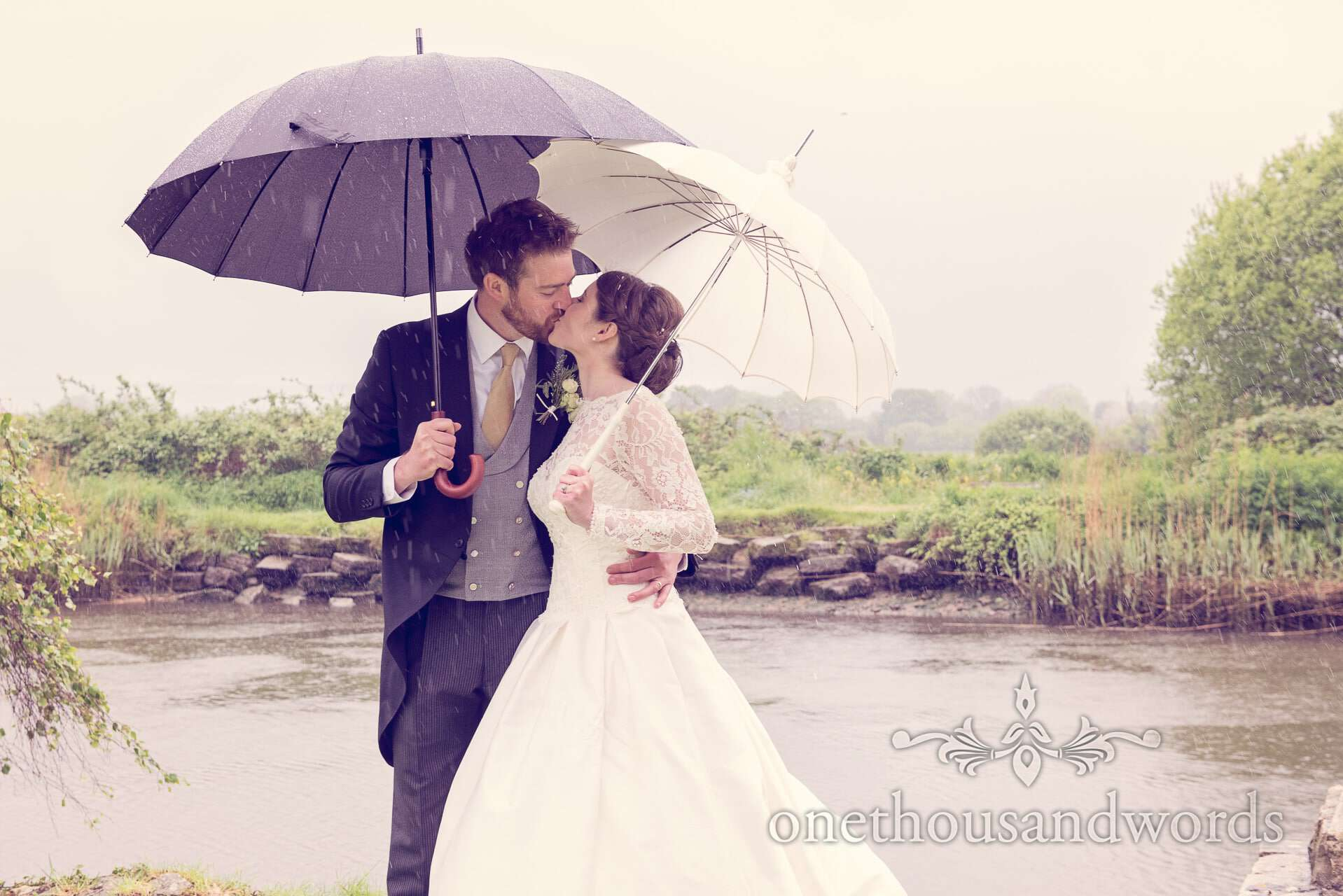 Bride and groom kiss under umbrellas in rain by Wareham river