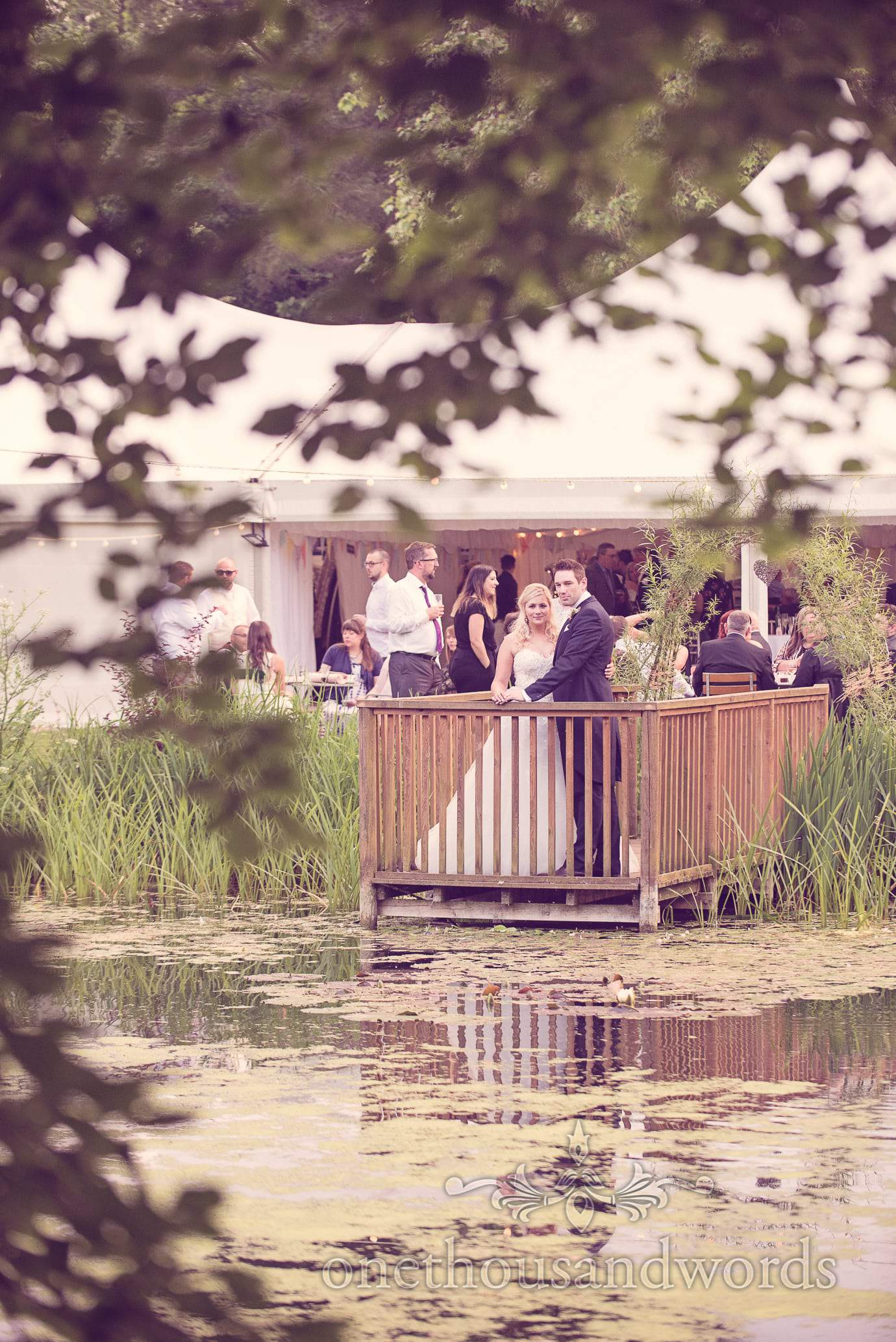 Bride and groom on pontoon next to lake at Deans Court Wedding