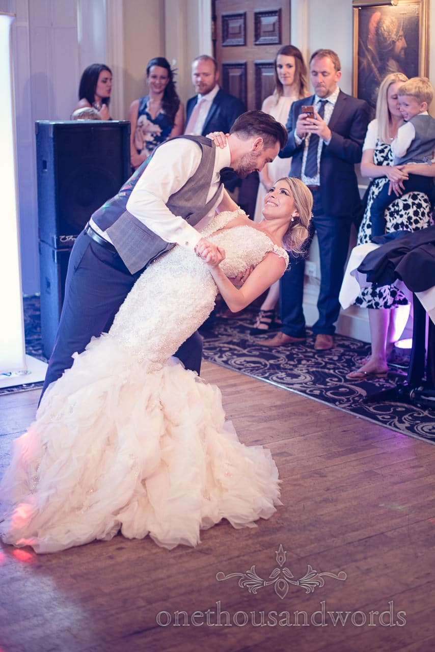 Bride and groom perform drop during first dance at Rhinefield House Wedding