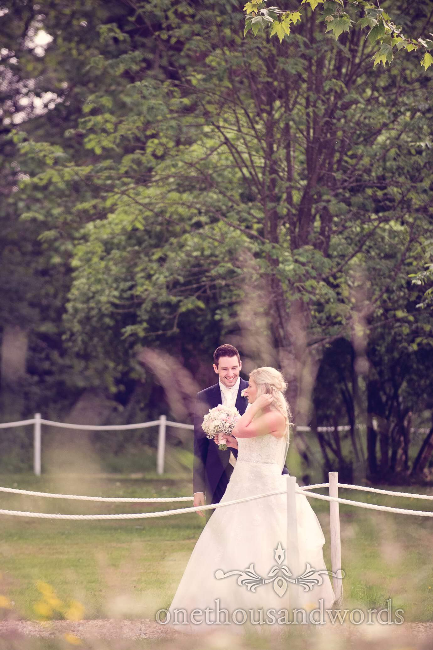 Bride and groom walk down path to marquee at Deans Court wedding