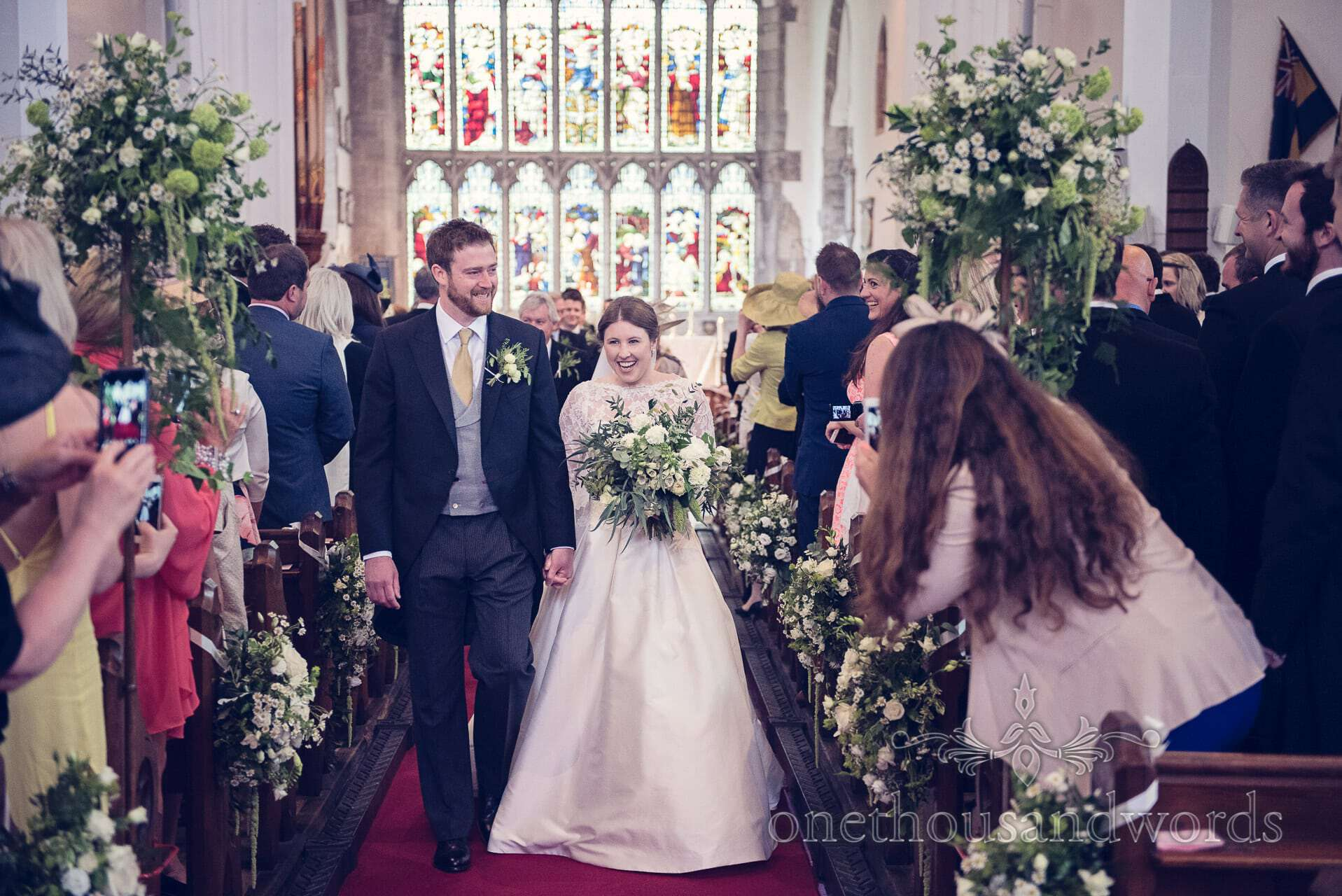 Bride and groom walk down the aisle at St Mary's church Wareham