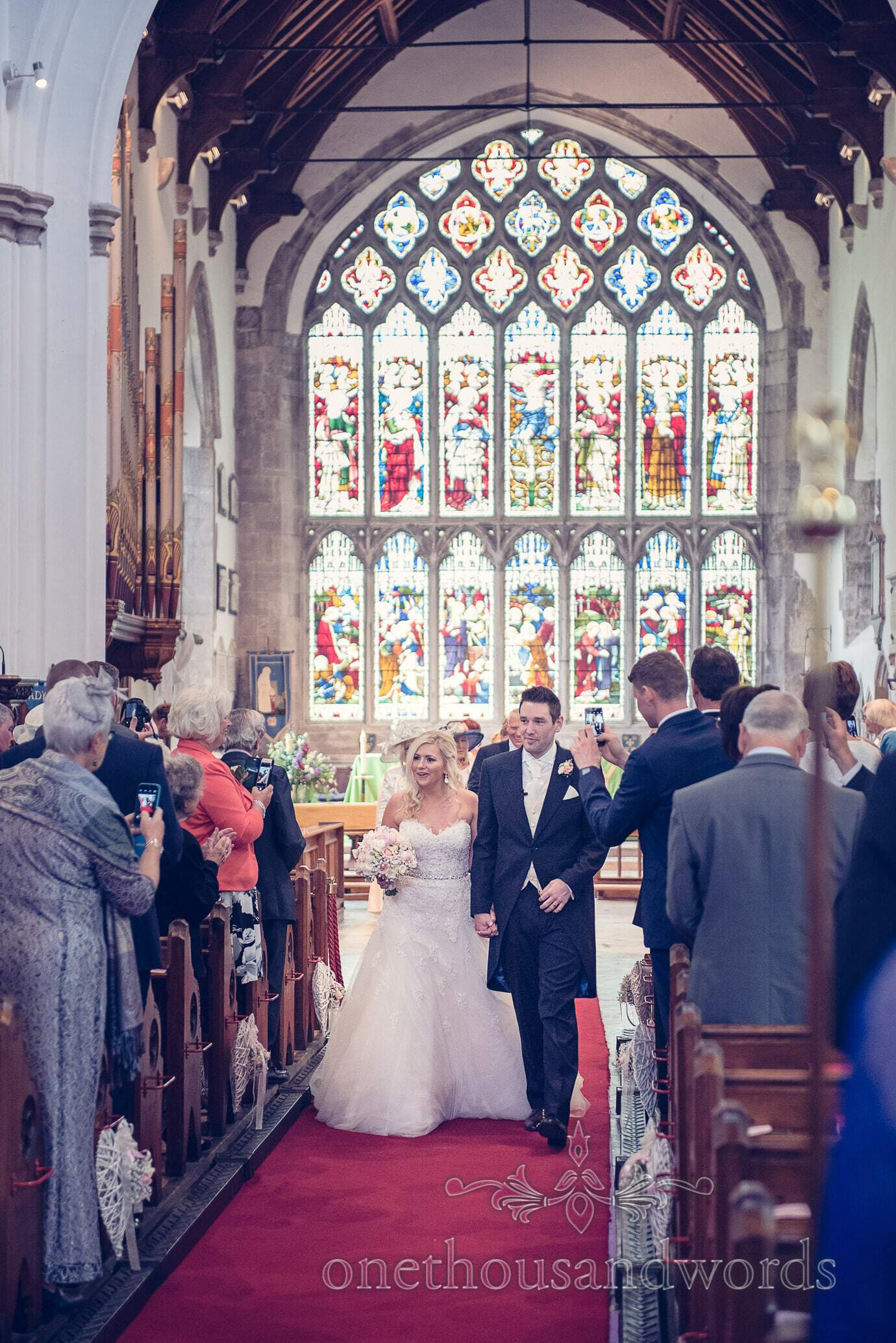 Bride and Groom walk down the aisle at St Marys Church wedding in Wareham