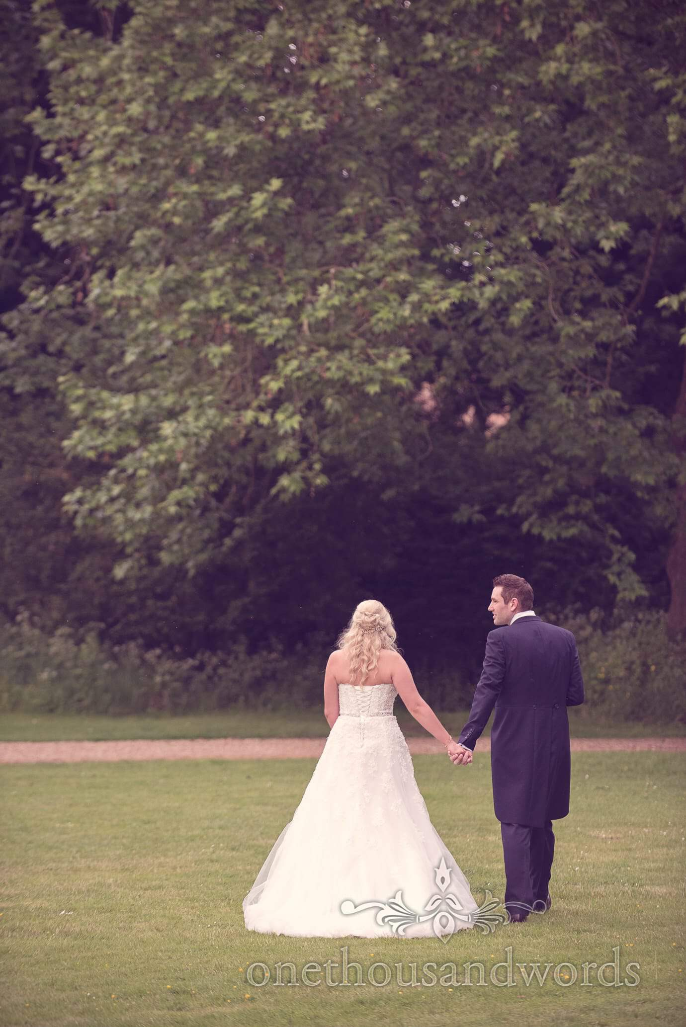 Bride and Groom walk through the gardens at Deans Court Wedding