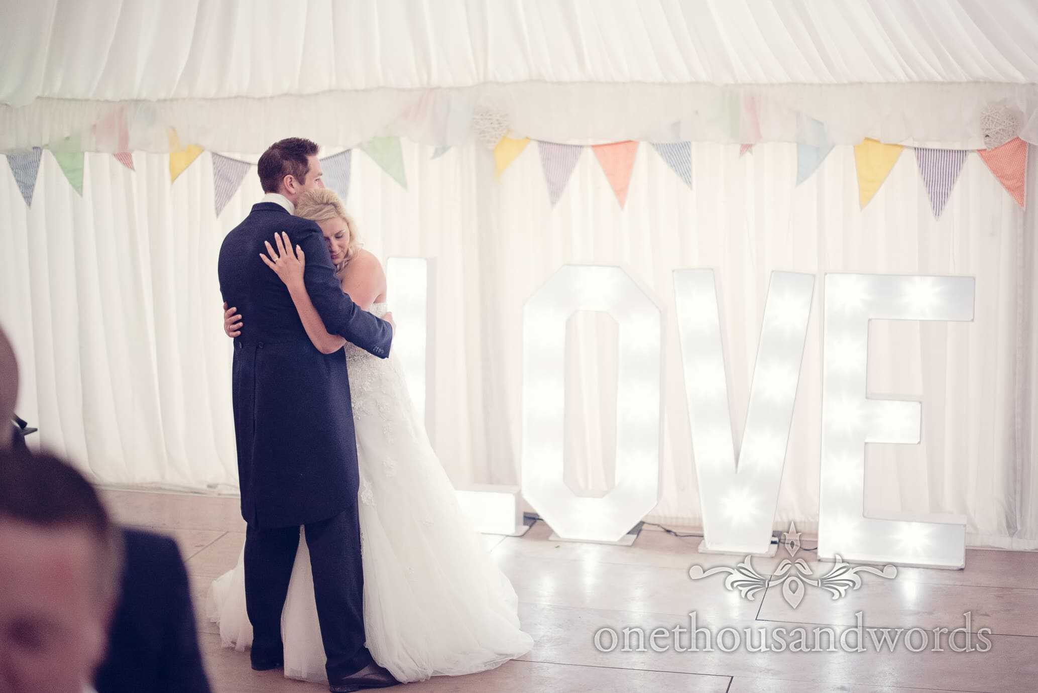 Bride and groom with love sign and wedding bunting dancing