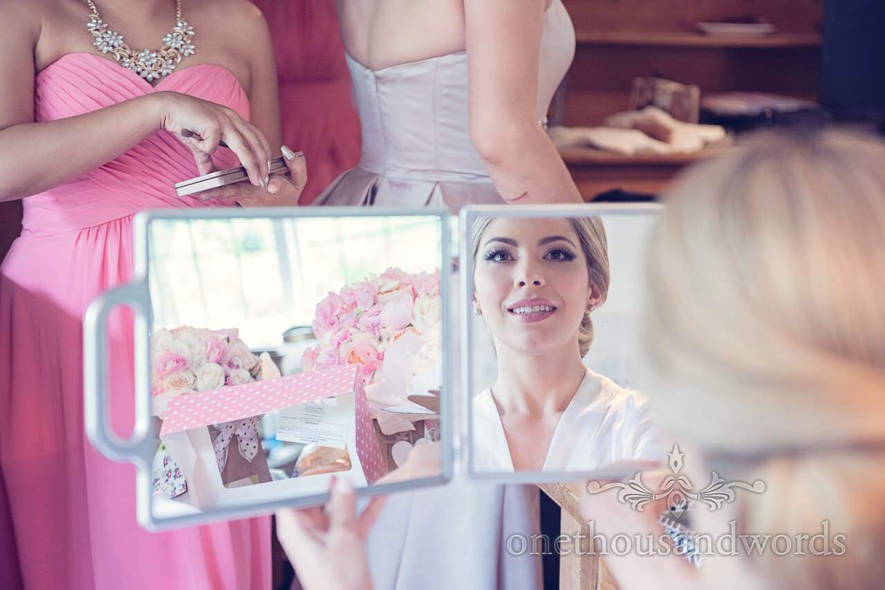 Bride and wedding flowers in makeup mirror on wedding morning