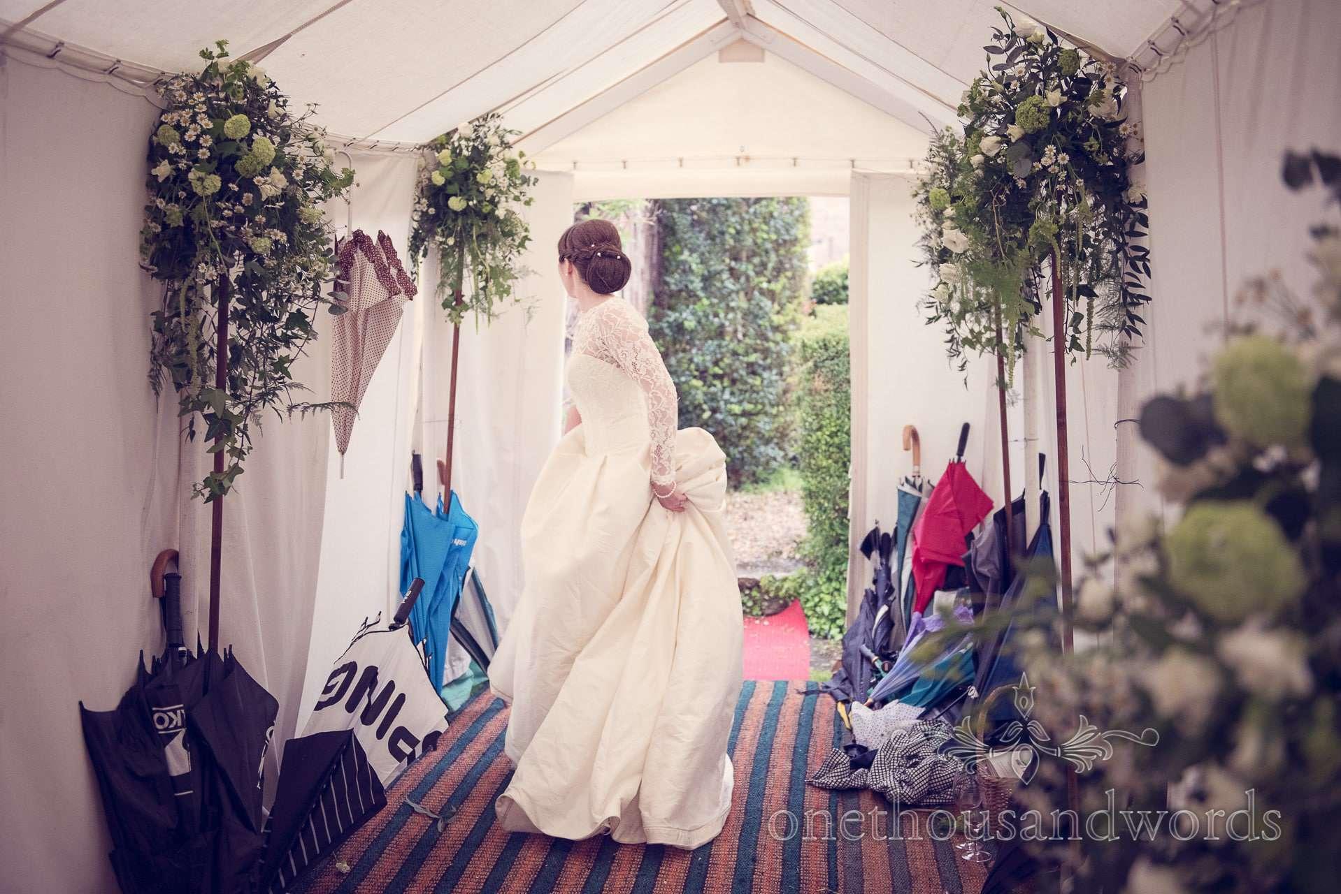 Bride arrives at wedding marquee with umbrellas