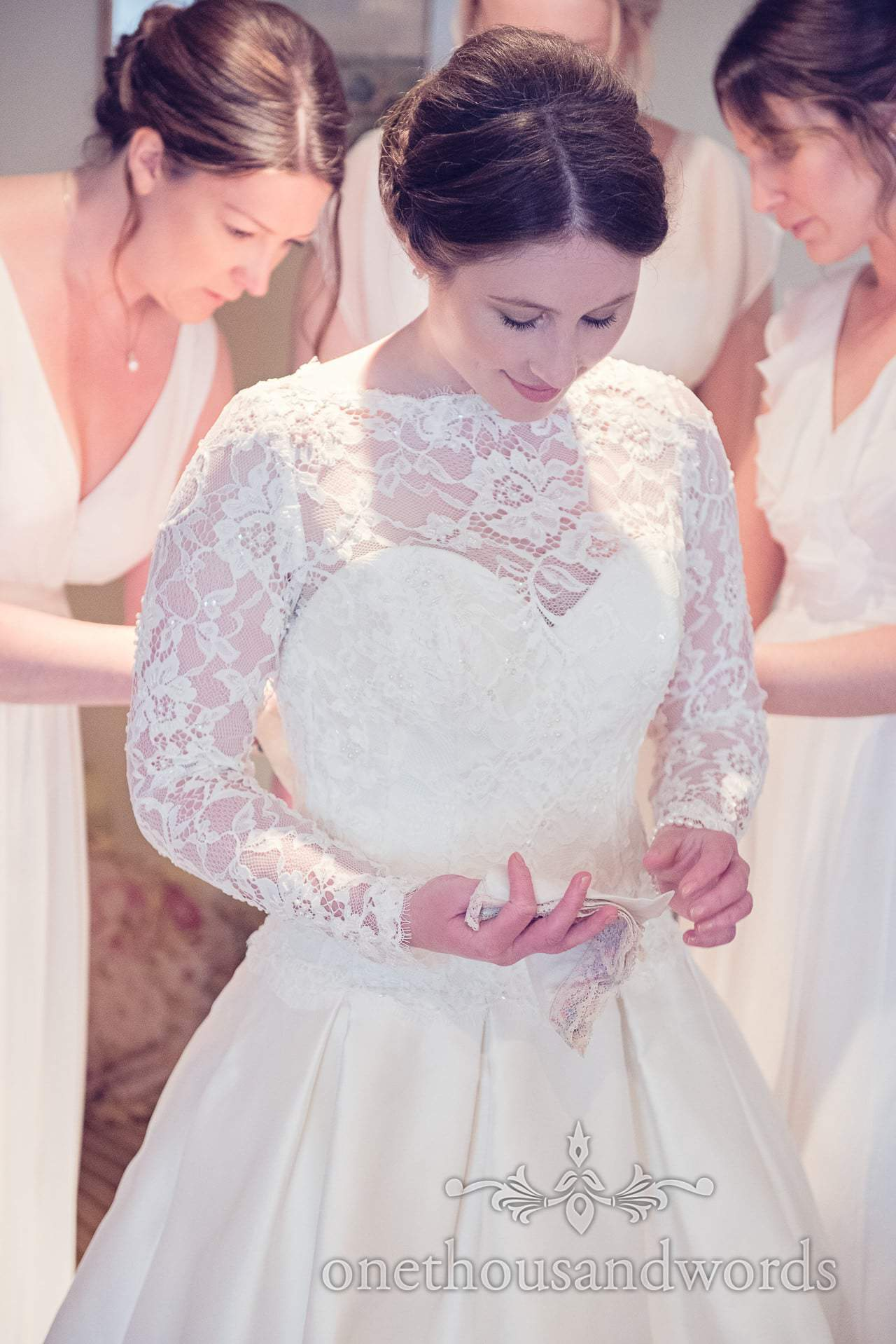 Bride being laced into wedding dress with antique handkerchief