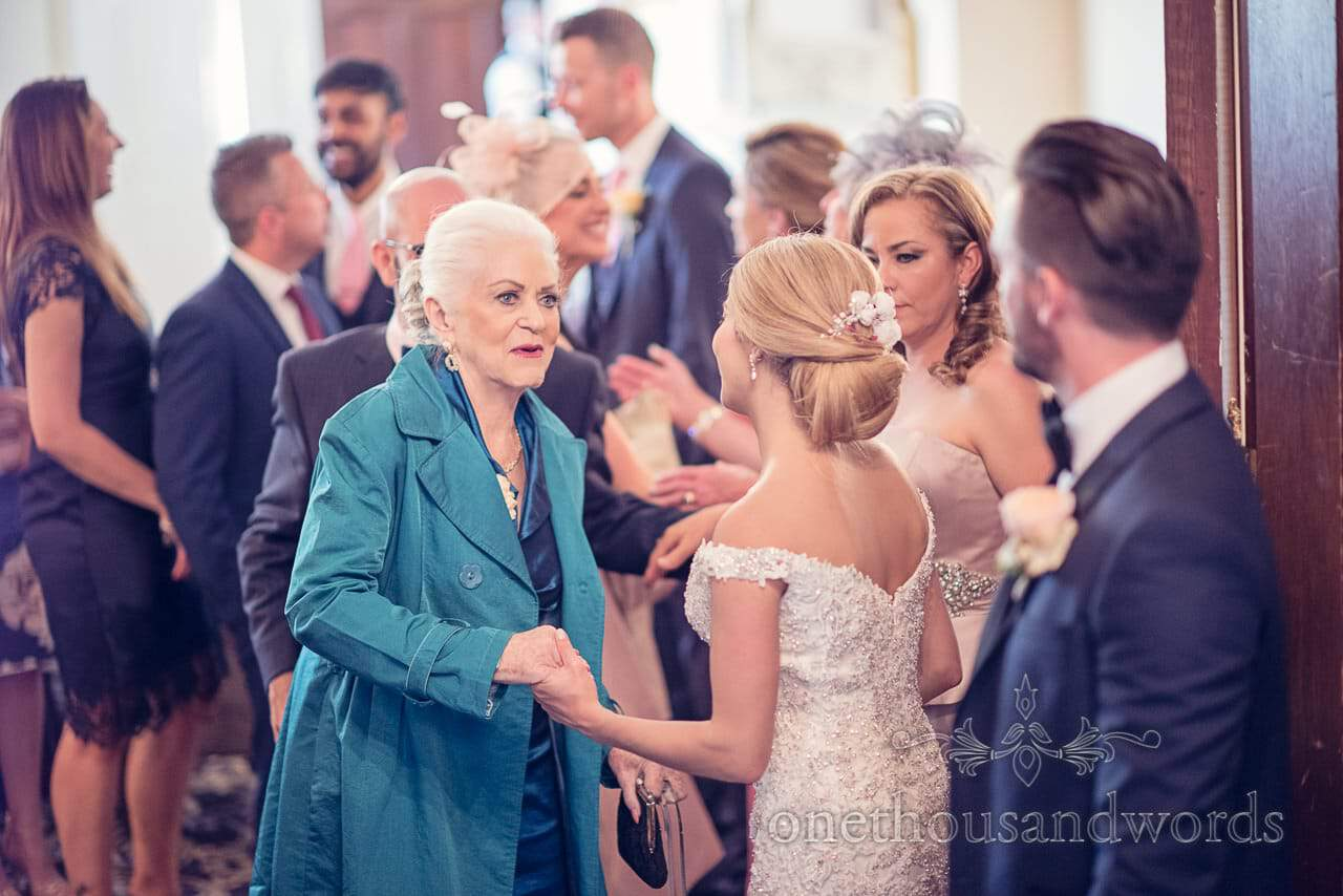 Bride greets guest in receiving line at Rhinefield House Wedding