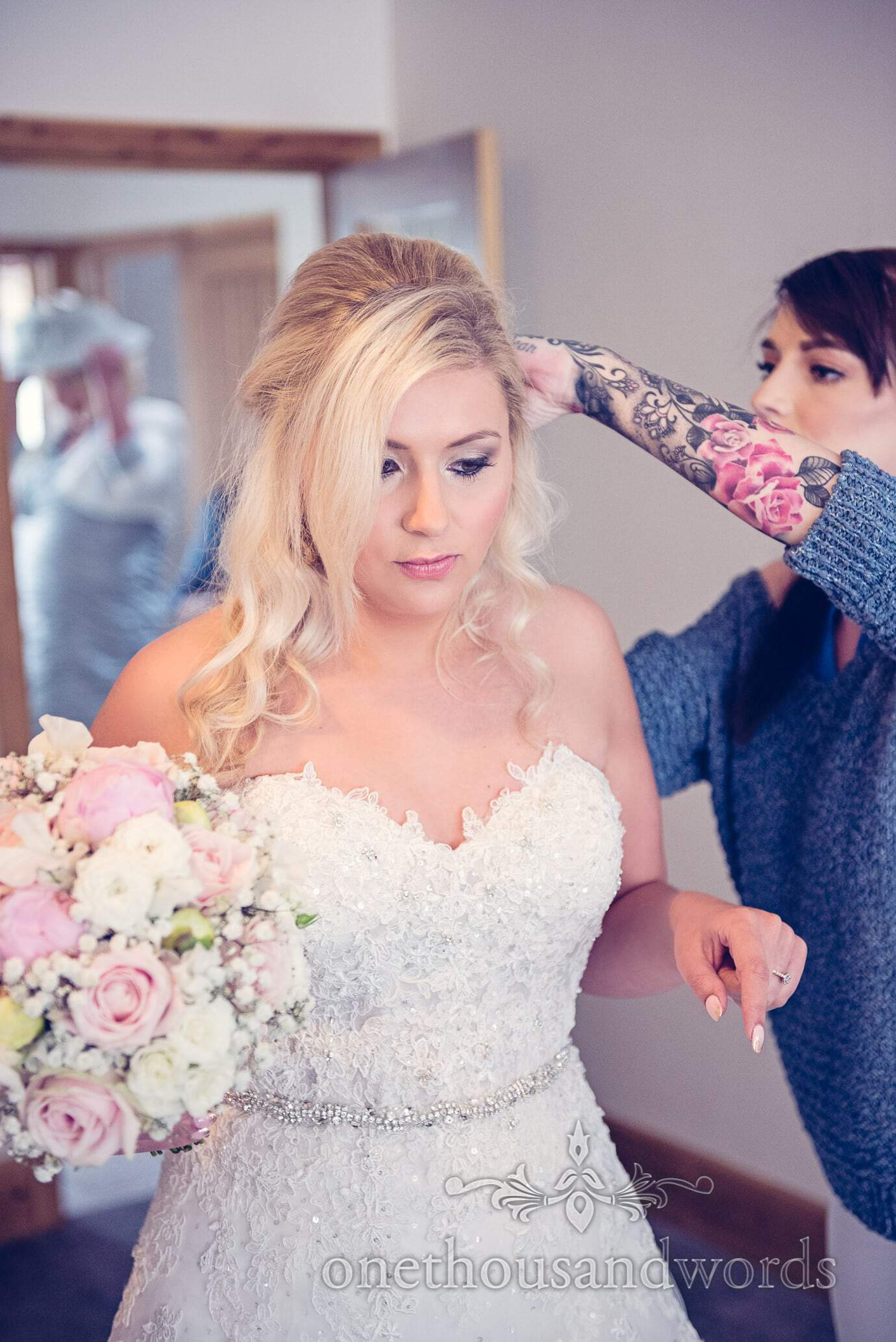 Bride has hair adjusted by wedding hair stylist with sleave tattoos