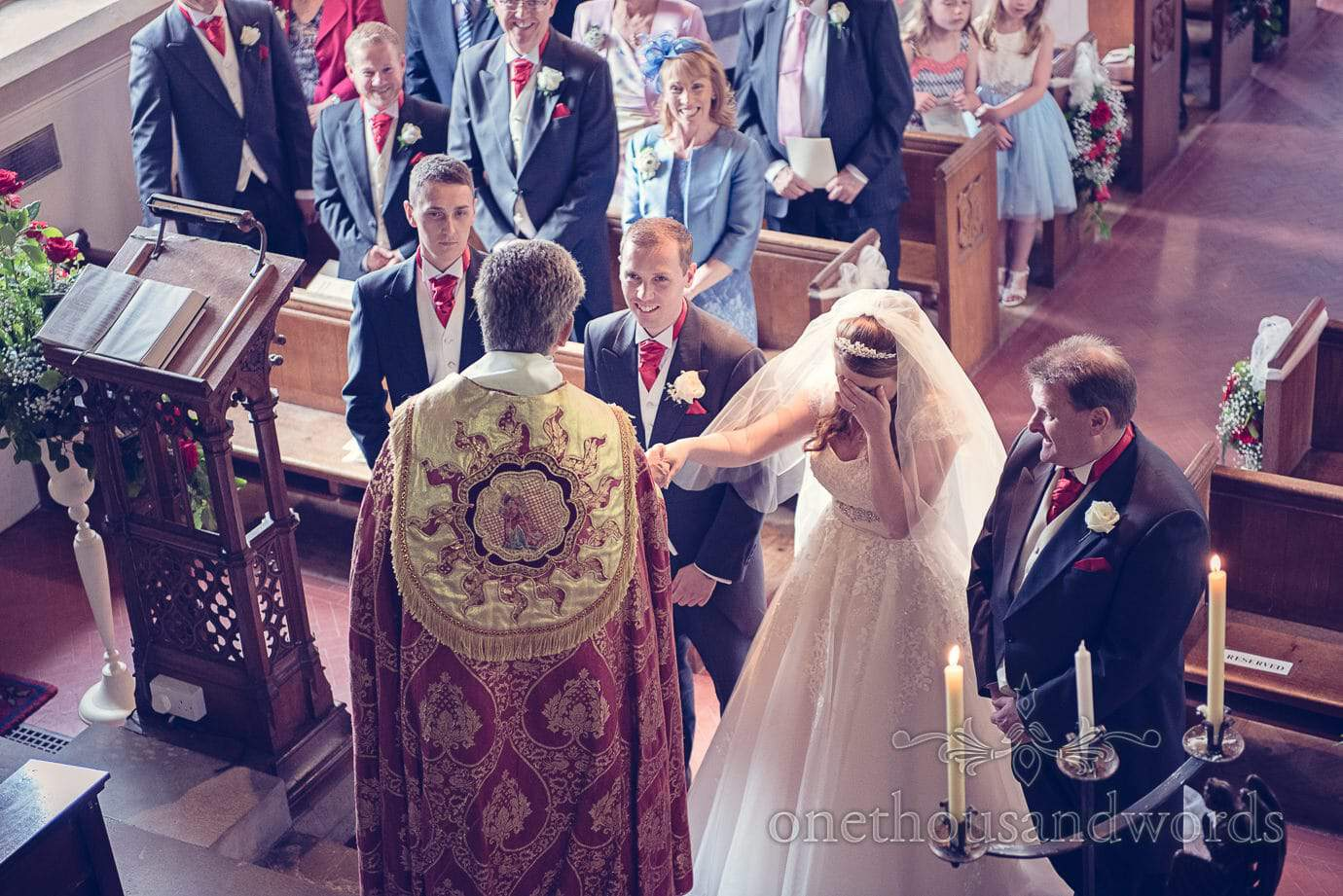 Bride hides her face at her father's joke during church wedding ceremony