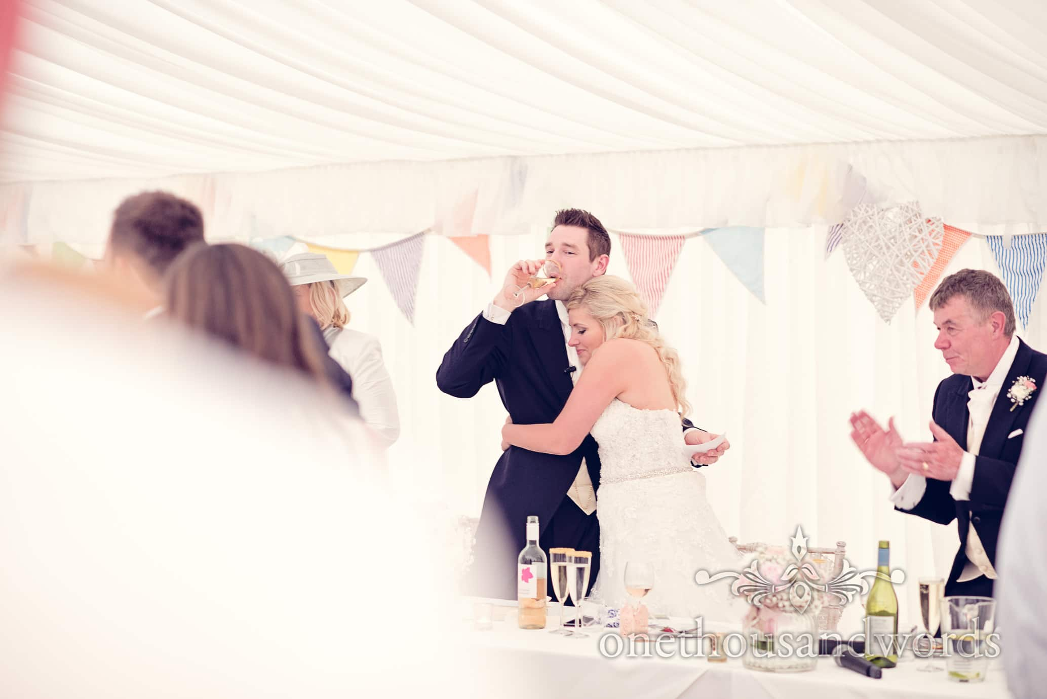 Bride hugs groom at the end of his wedding speech at Deans Court Wedding