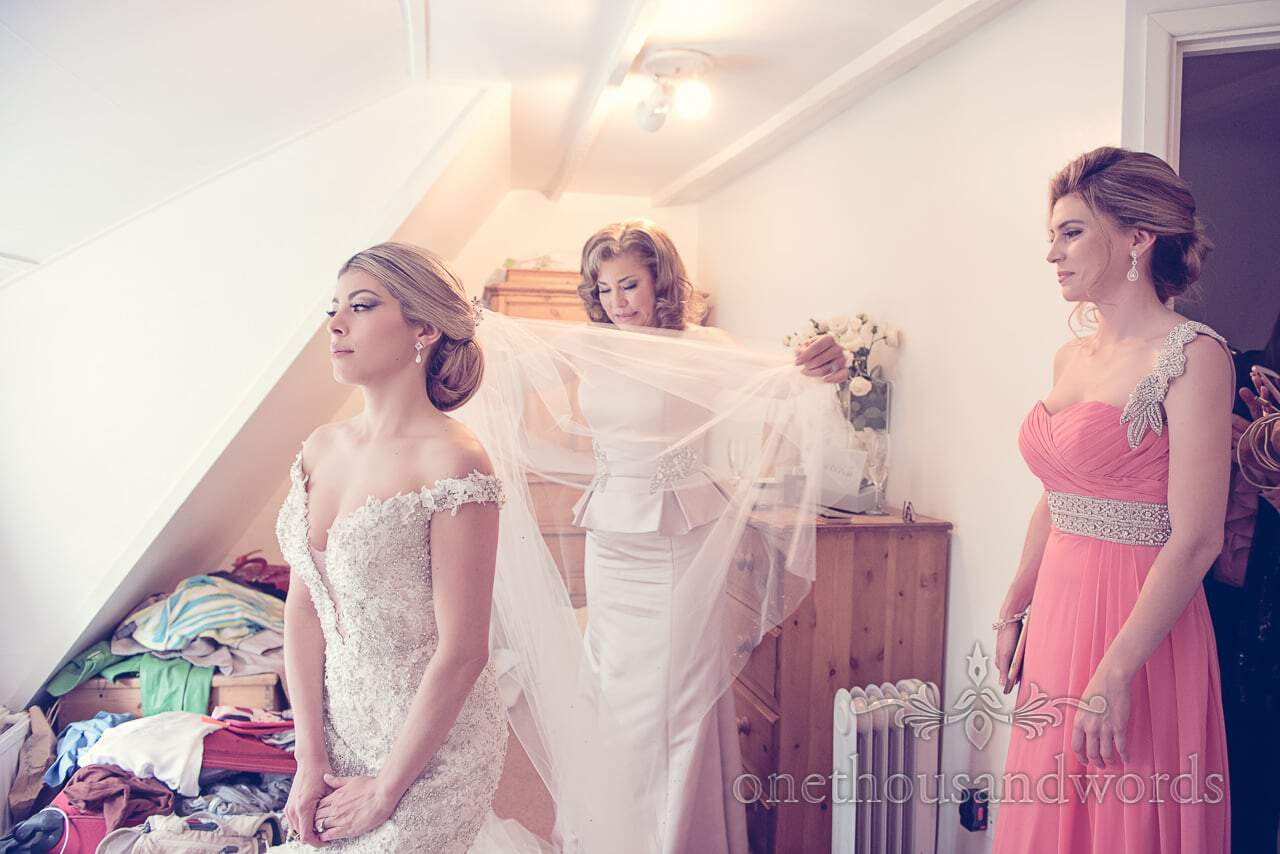 Bride in jewled white wedding dress with veil on wedding morning