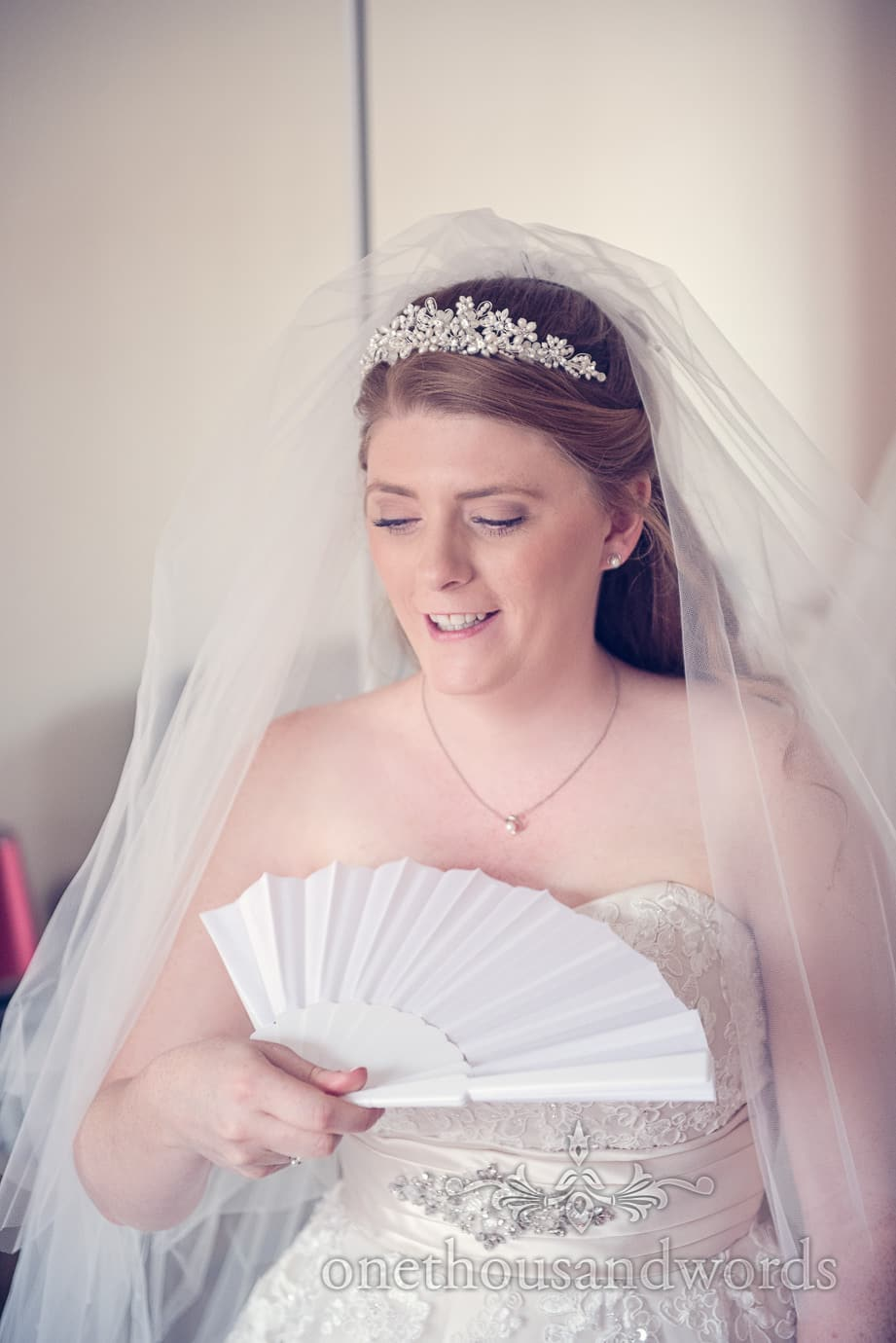 Bride in tiara and veil uses white wedding fan on Dorset wedding morning