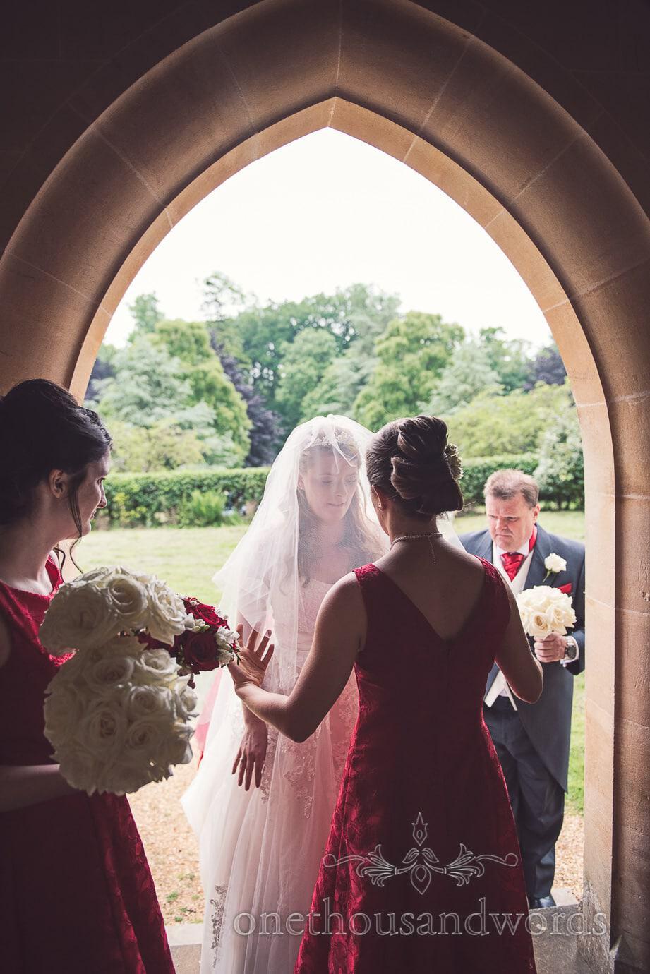 Bride in wedding veil under stone church arched doorway