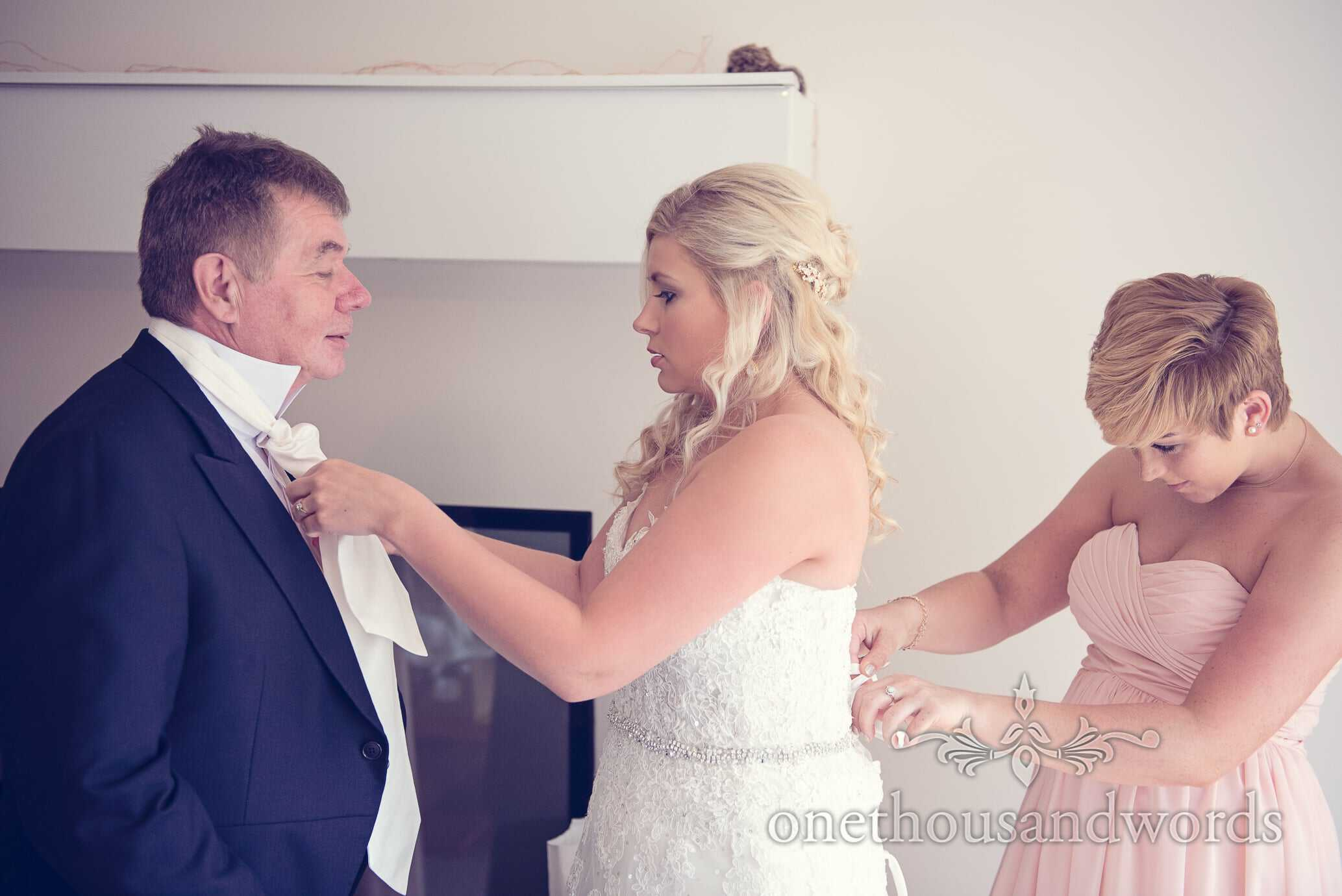 Bride is laced into wedding dress by bridesmaid as she adjusts her fathers cravatte