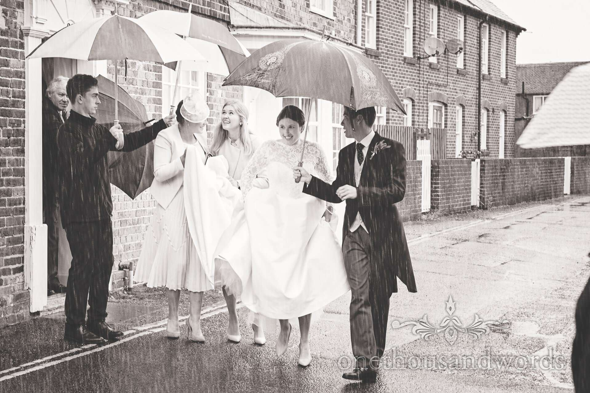 Bride leaves for wedding in the rain under umbrellas