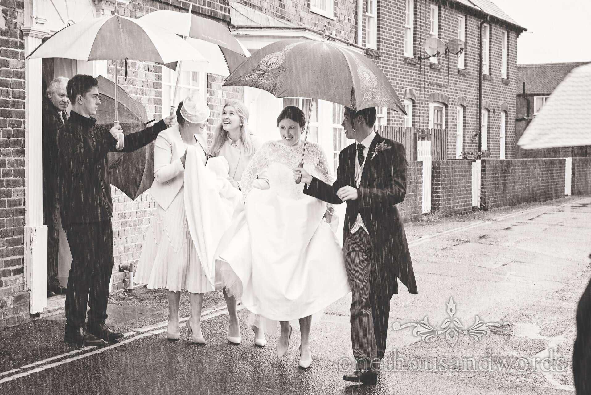 Bride leaves for wedding in the rain under umbrellas
