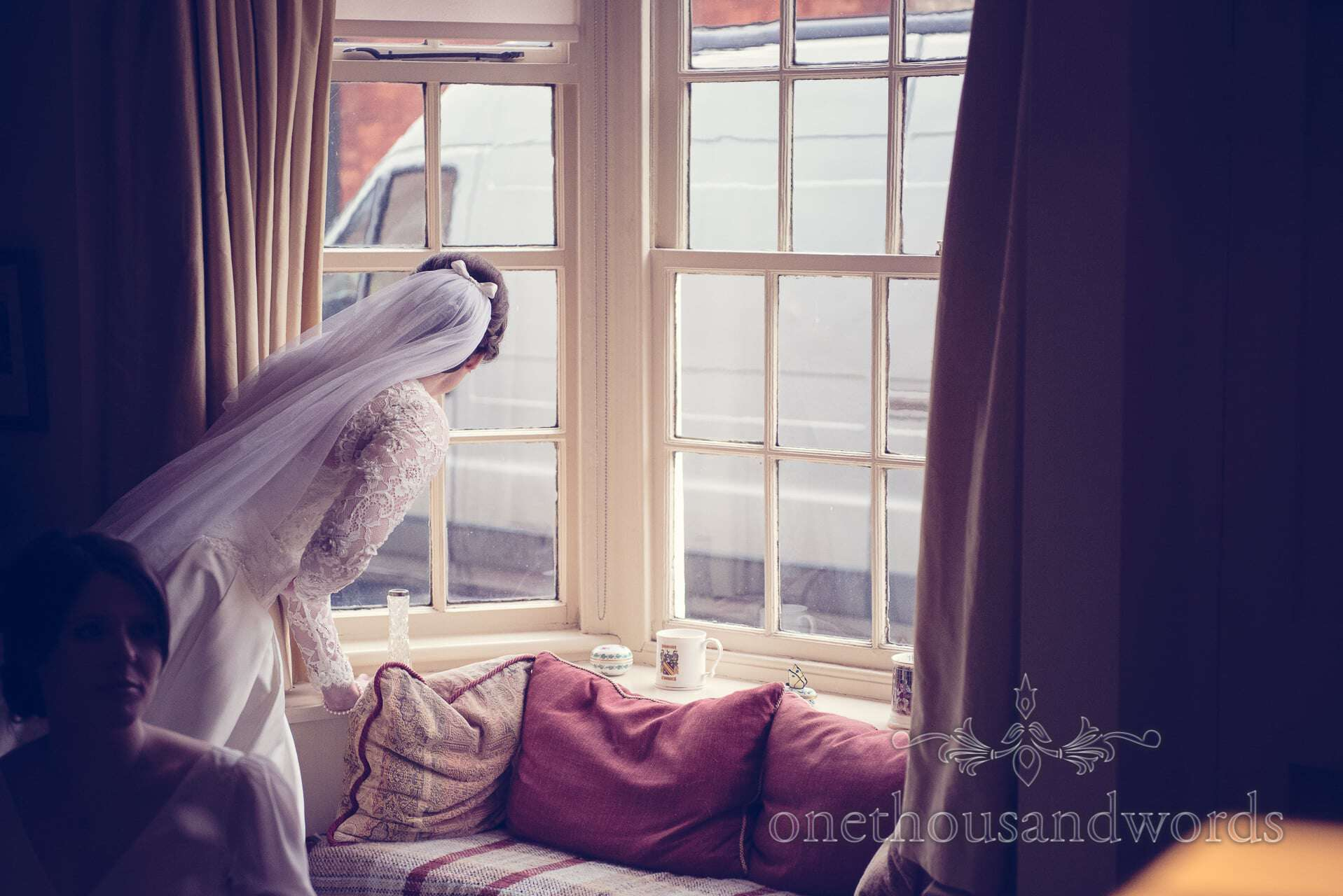 Bride looks out of window for wedding guests
