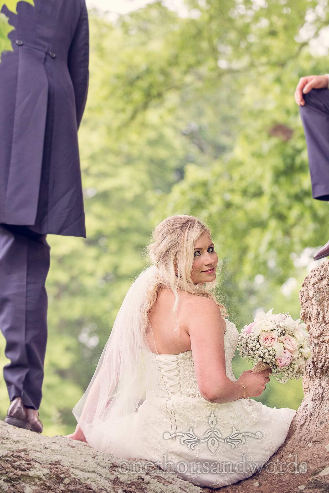 Bride looks over her shoulder in a tree at Deans court wedding