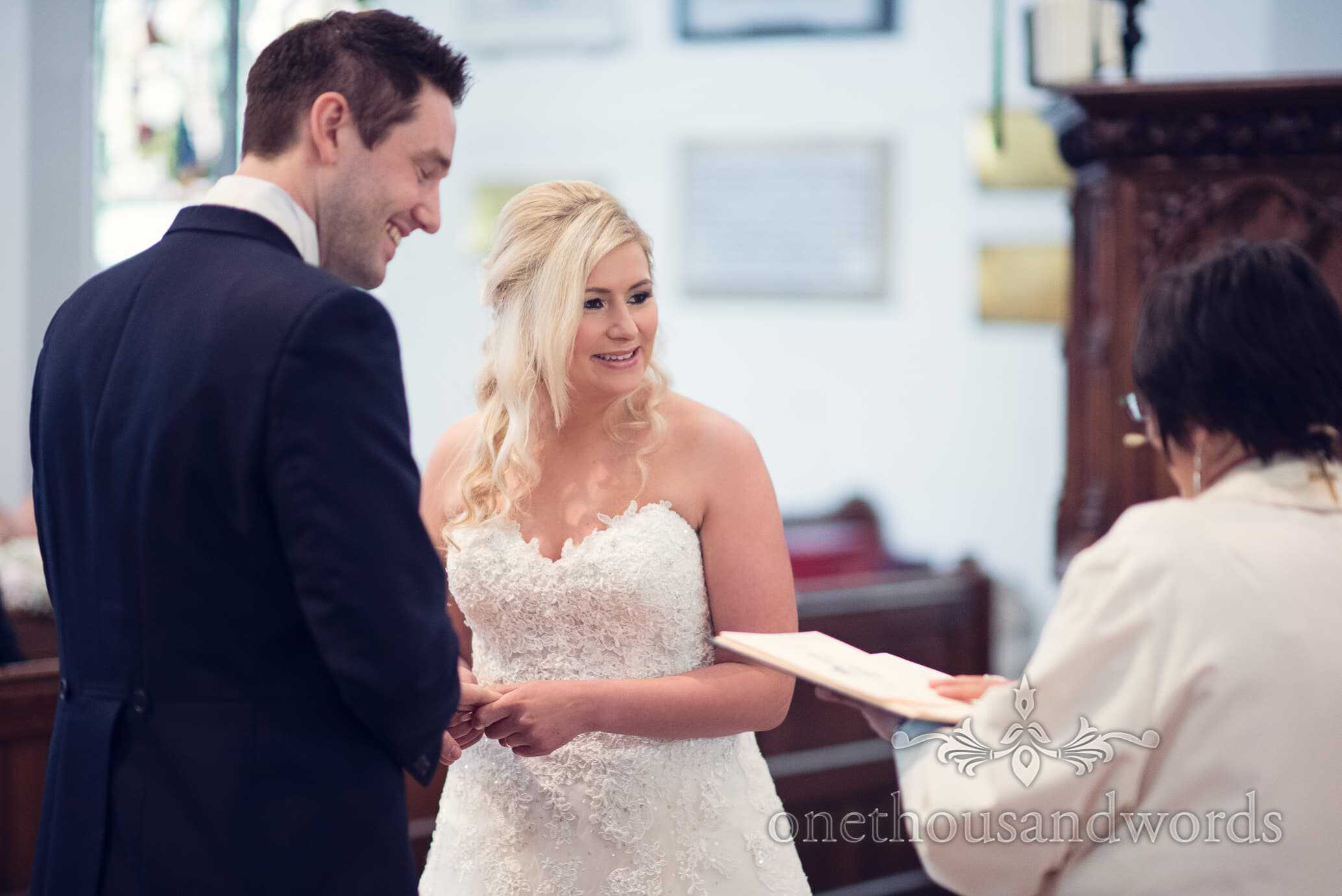 Bride smiles during exchange of the rings at Wareham church wedding