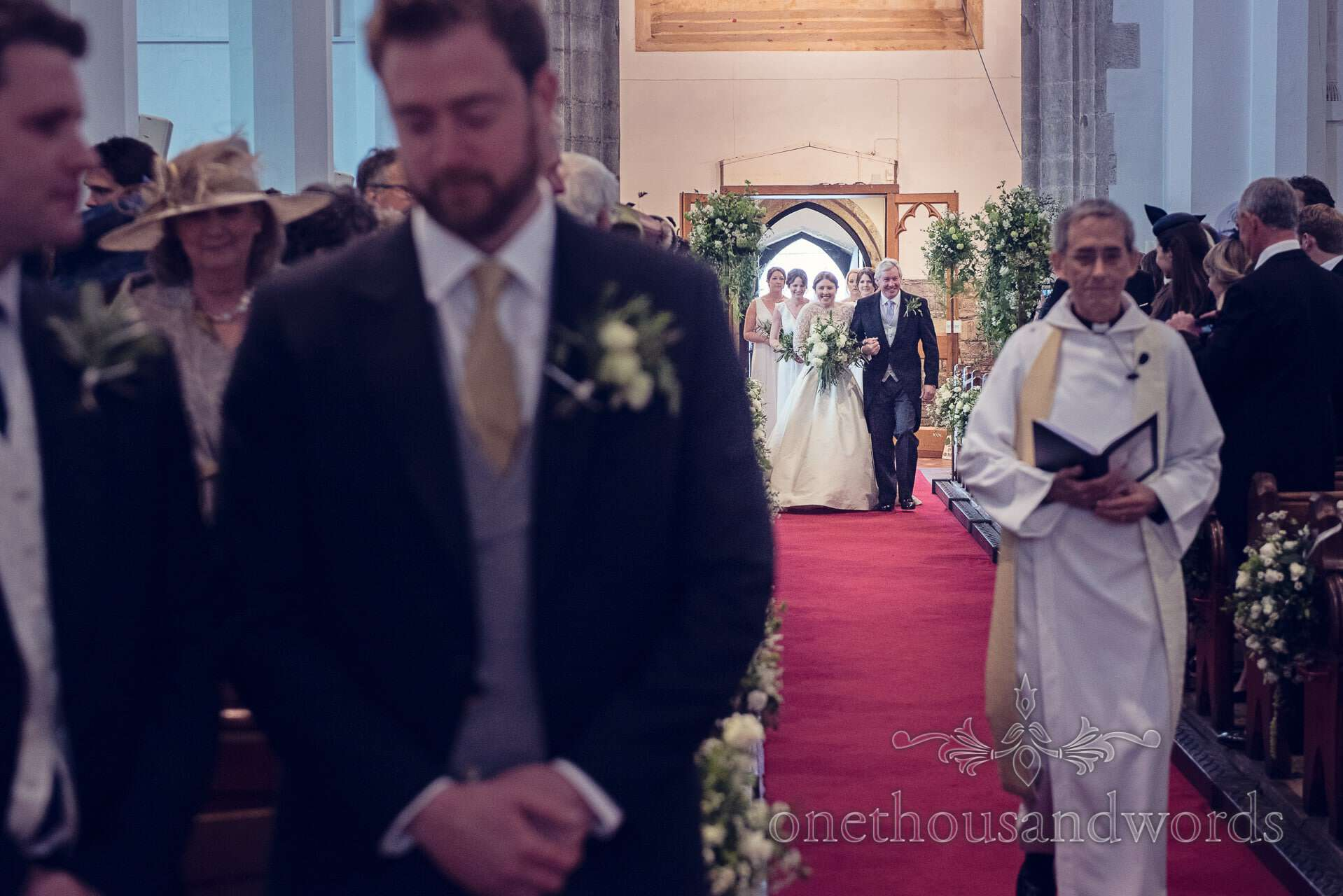 Bride walks down the aisle at St Mary's Church Wareham wedding