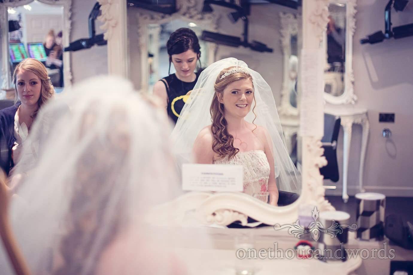 Bride wears veil in hairdressers mirror on wedding morning