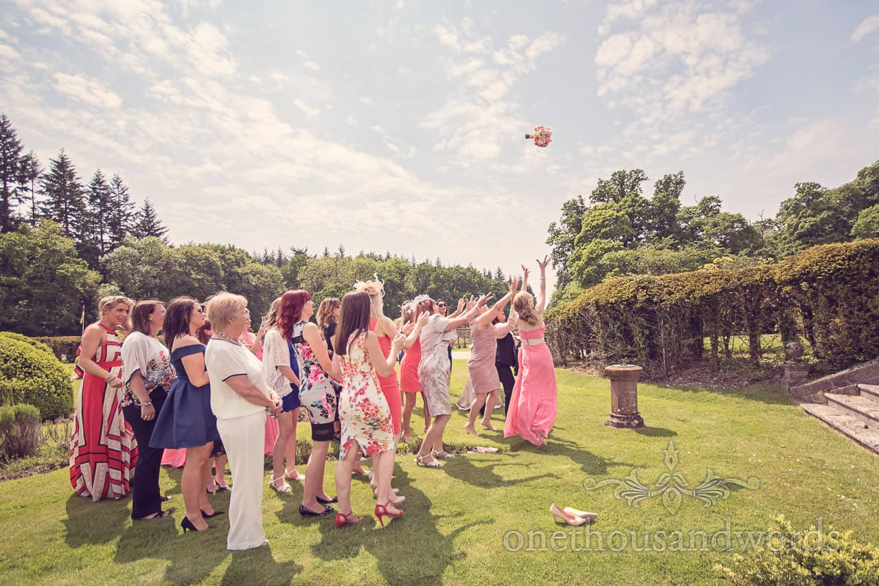 Brides bouquet in the air at Rhinefield House Wedding