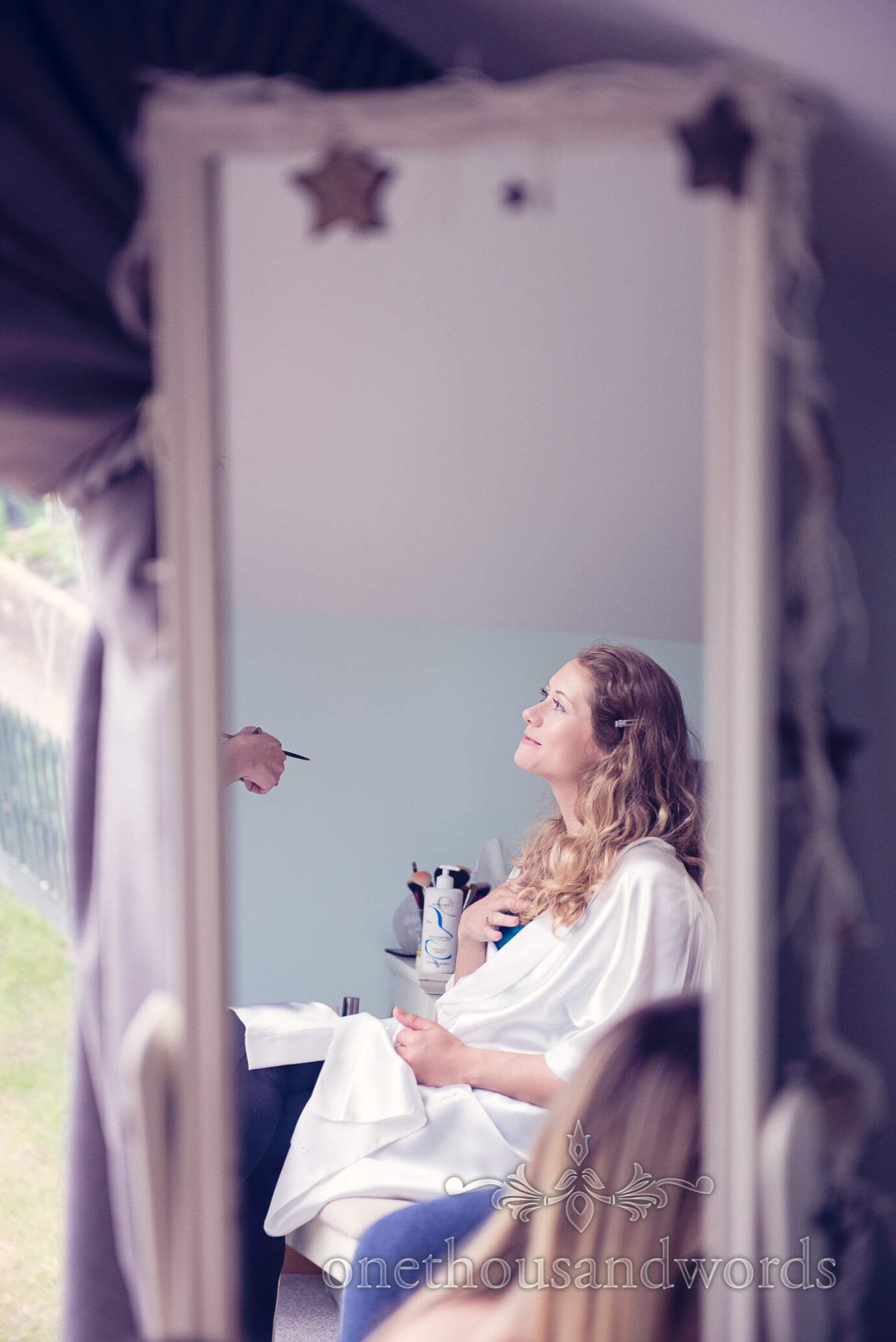 Bridesmaid has makeup styled in mirror on wedding morning