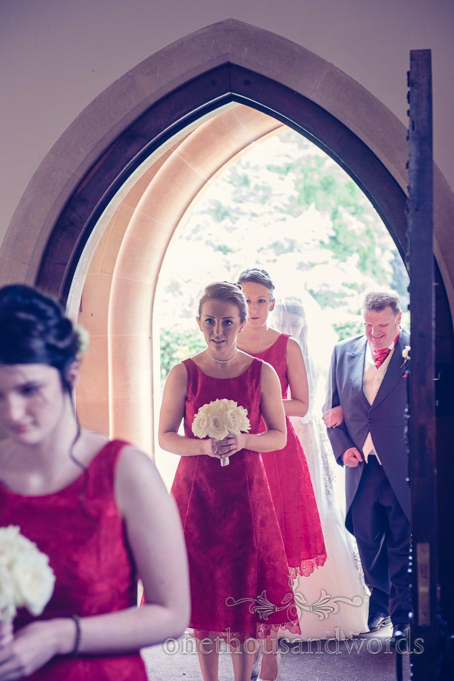 Bridesmaid in red bridesmaid dress enters church wedding ceremony