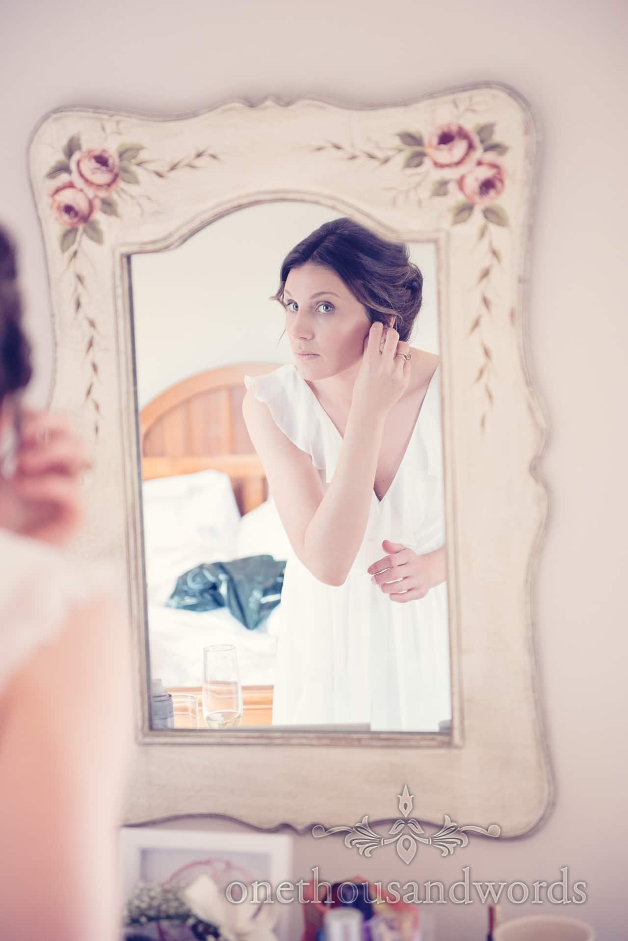 Bridesmaid looks in mirror during wedding morning preparations