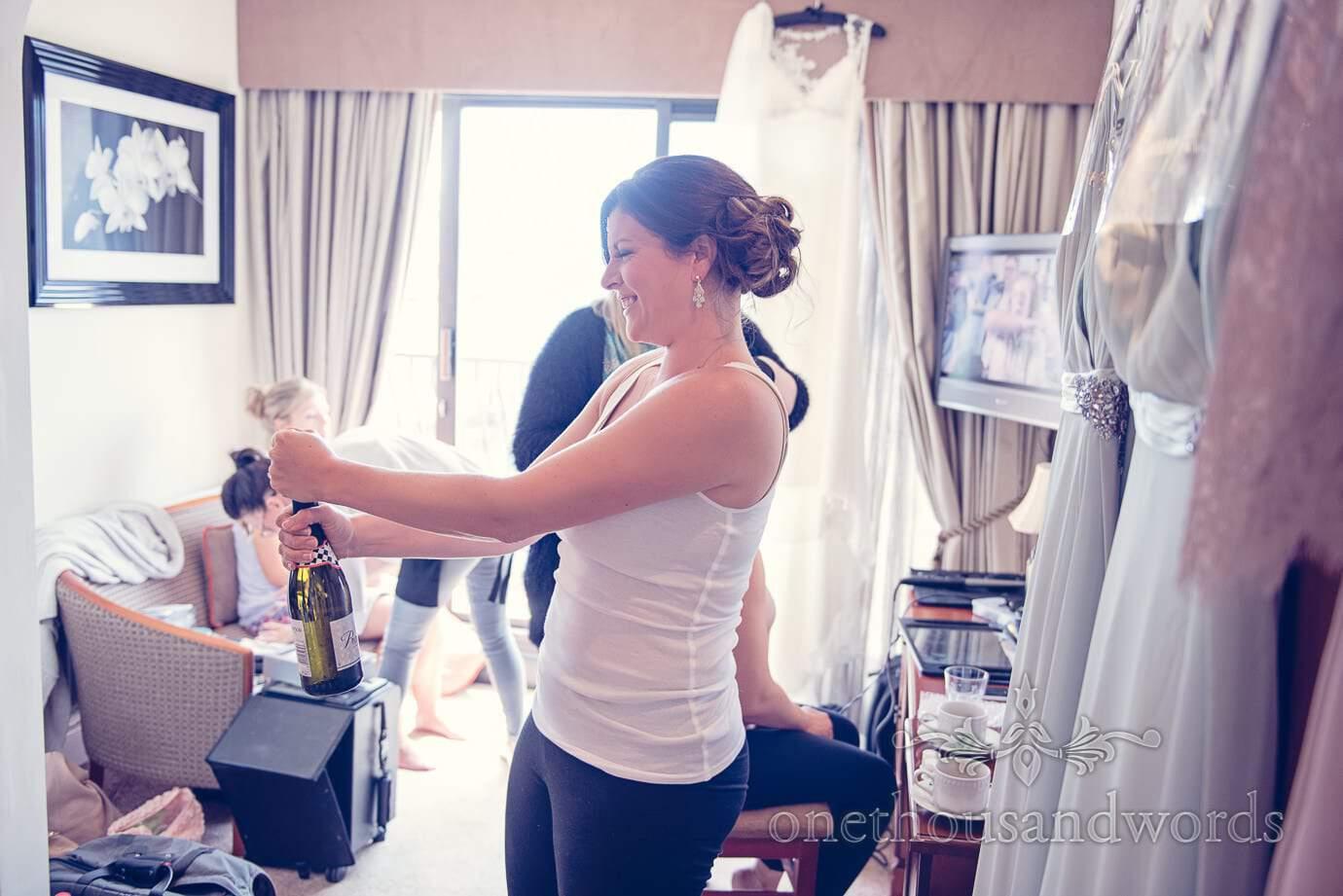 Bridesmaid opens champagne at Italian Villa Wedding Photographs