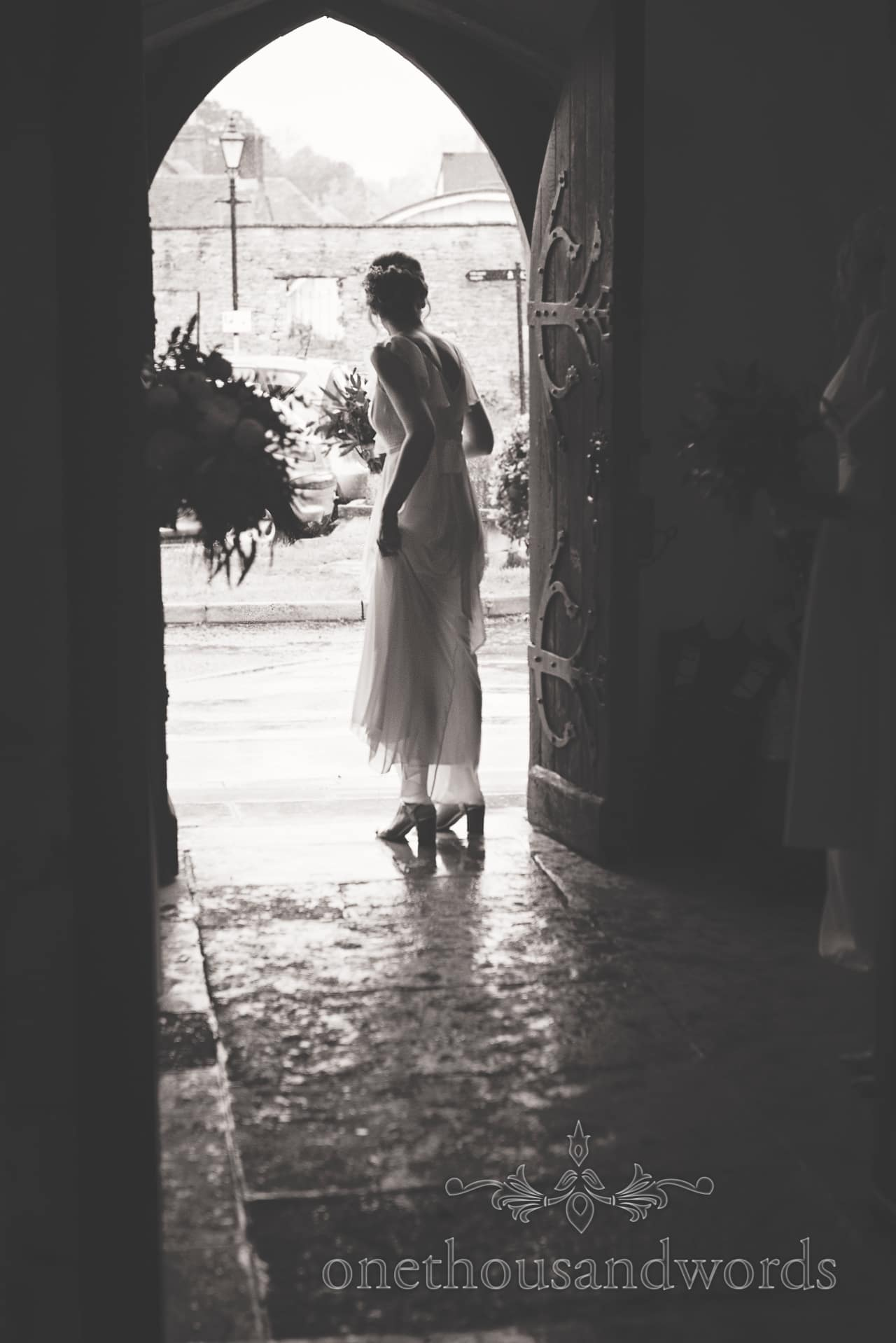 Bridesmaid waits for bride to arrive in church doorway