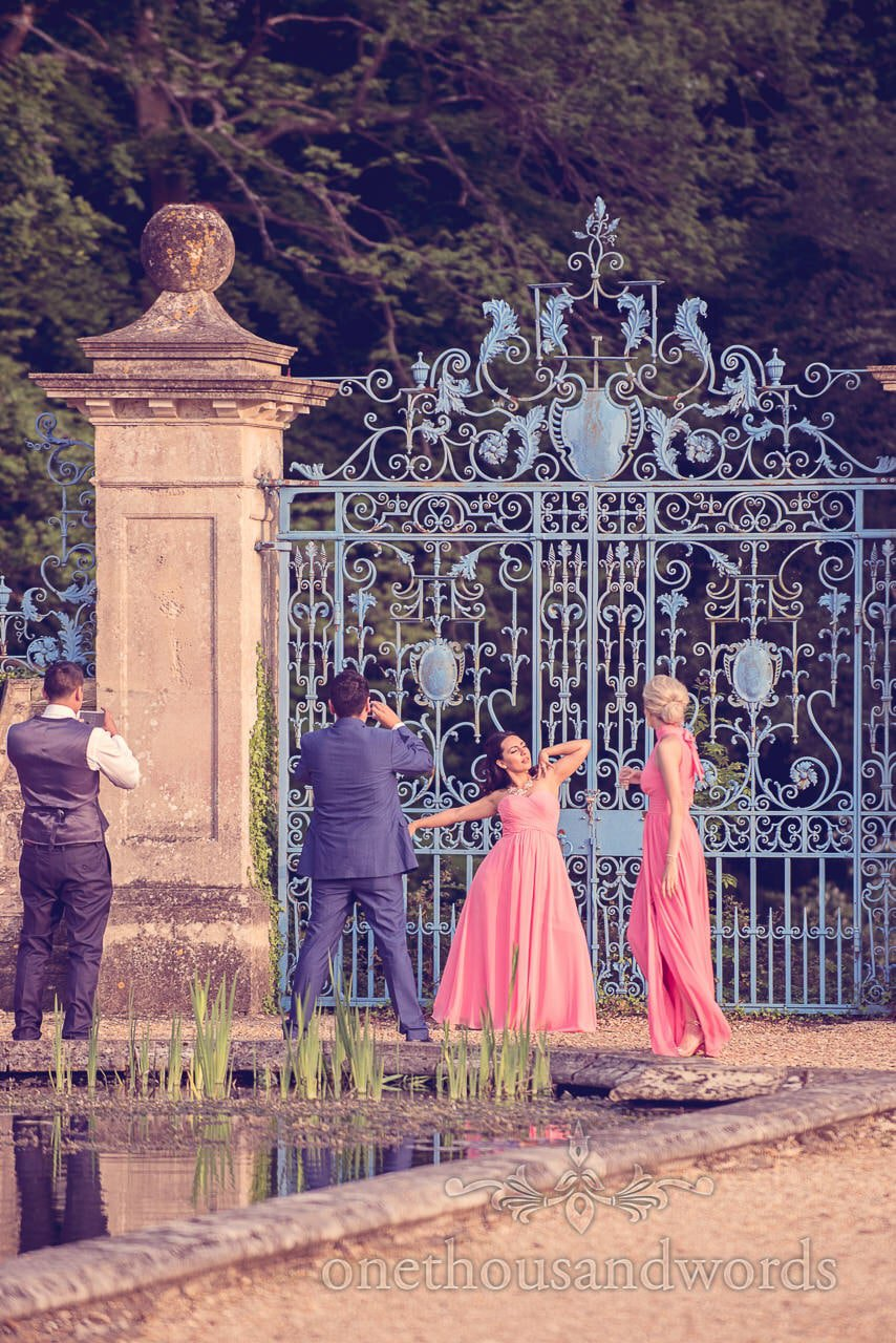 Bridesmaids in pink strike a pose by blue gates at Rhinefield House Wedding