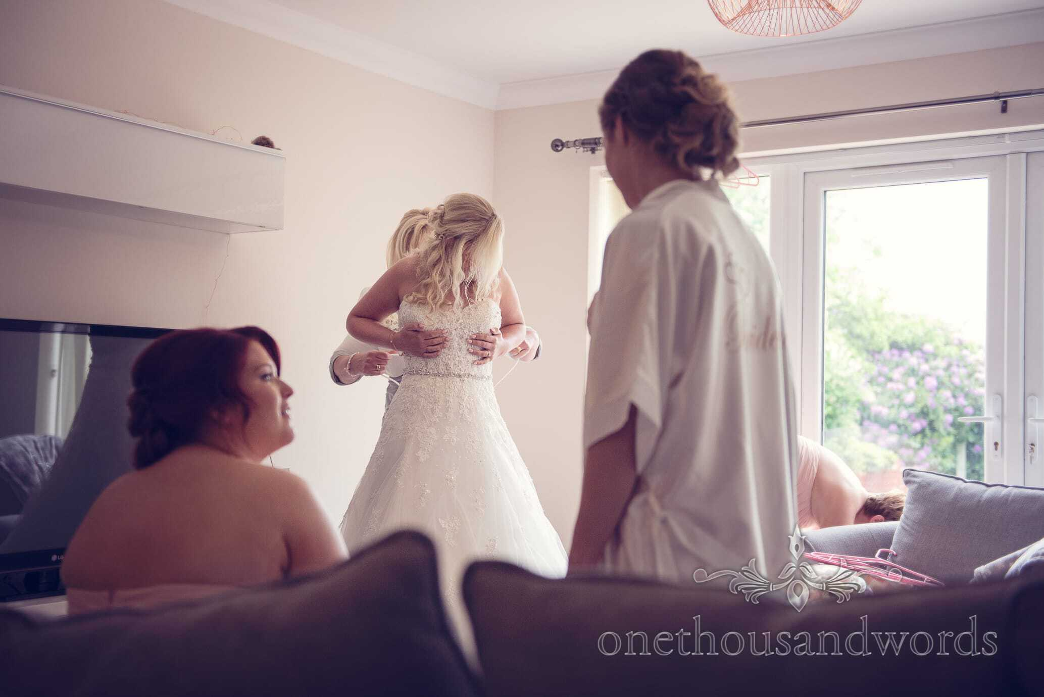 Bridesmaids watch bride being laced into wedding dress on wedding morning