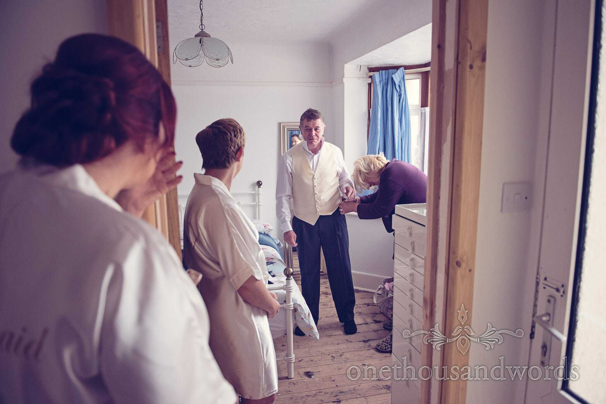 Bridesmaids watch father of bride being dressed on wedding morning