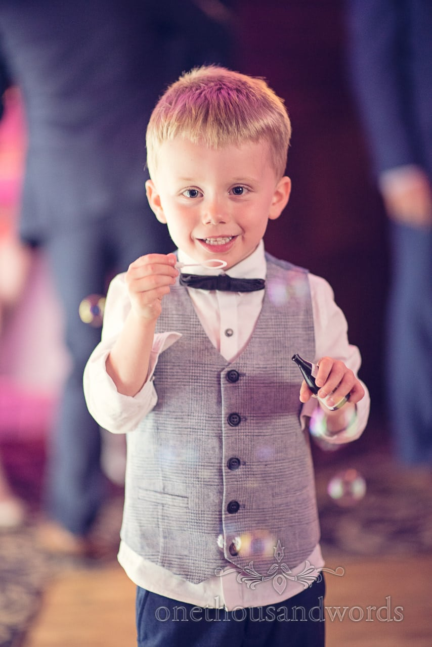 Child wedding guest blows bubbles on dance floor at Rhinefield House Wedding