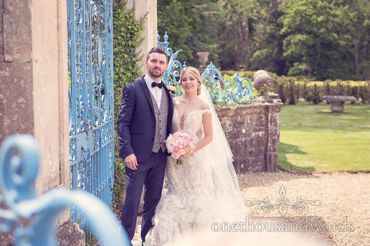 Couple by blue gates at Rhinefield House Wedding