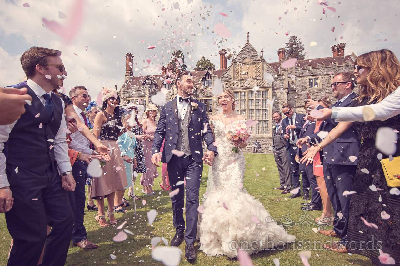 Couple in confetti shower at Rhinefield House Wedding