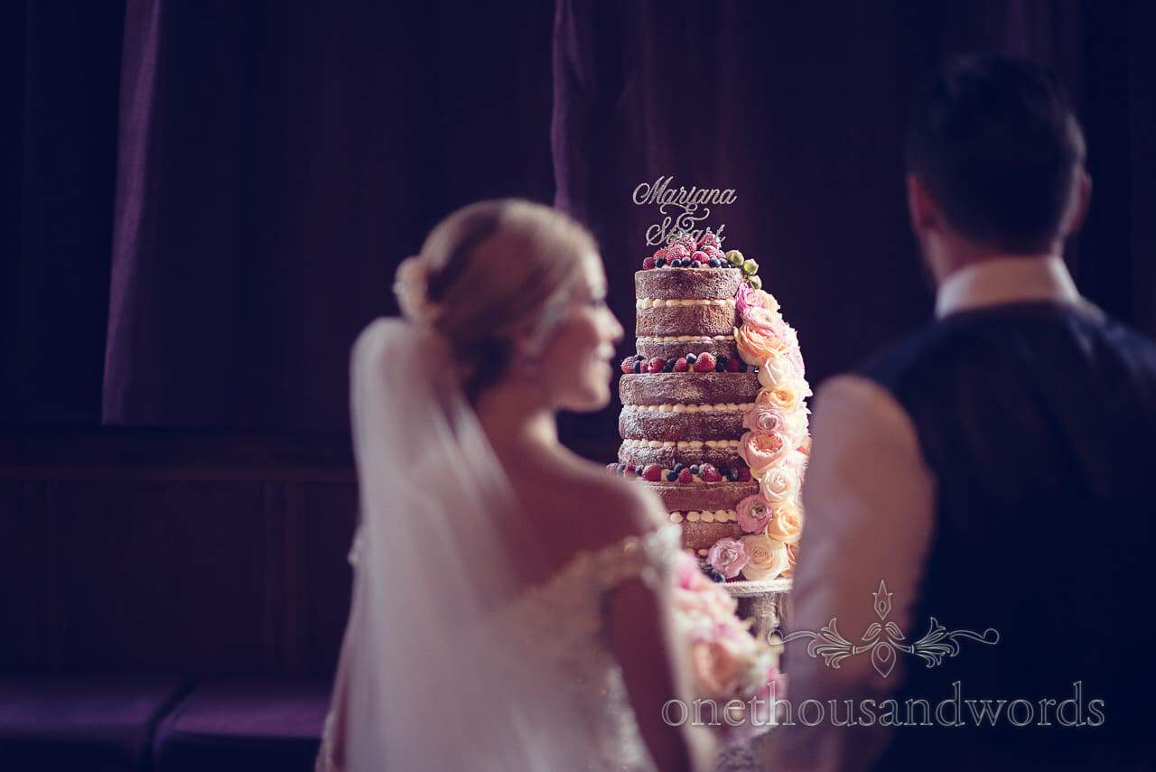 Couple in front of wedding cake at Rhinefield House Wedding